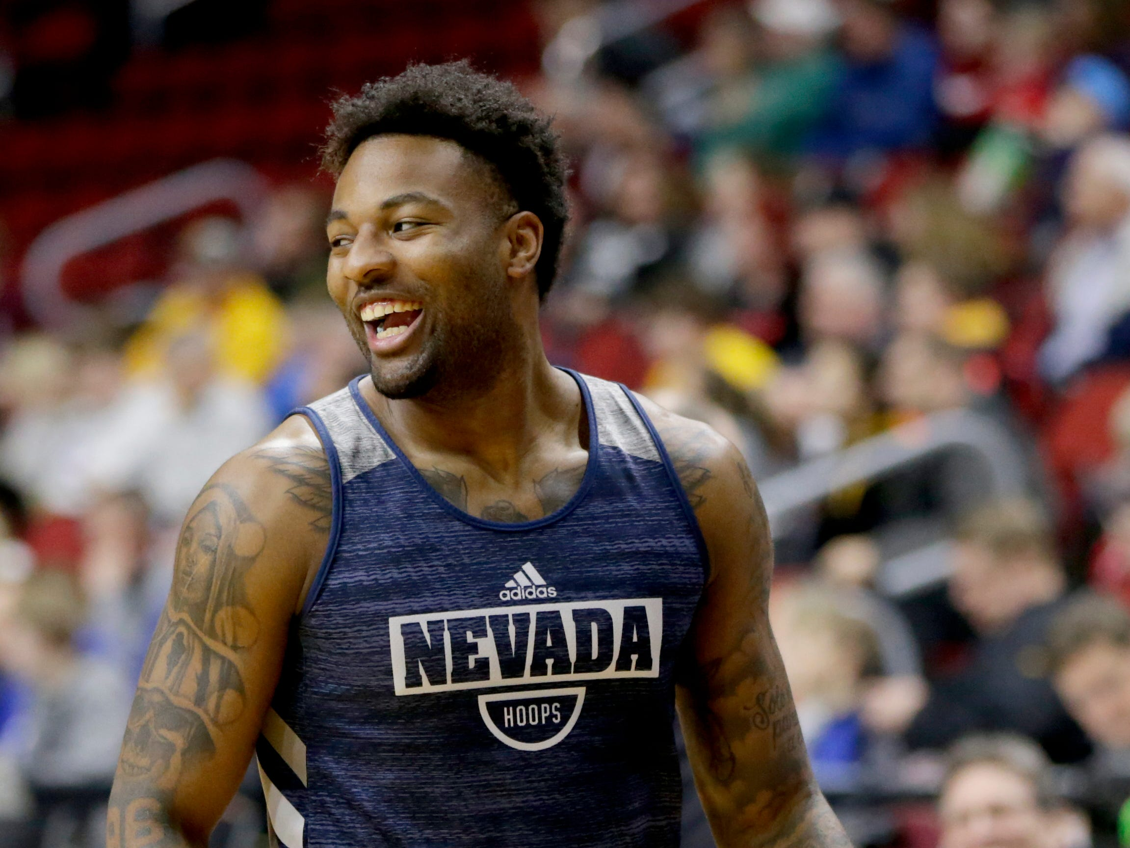 Nevada's Jordan Caroline smiles during team practice ahead of a first round men's college basketball game against Florida in the NCAA Tournament in Des Moines, Iowa, Wednesday, March 20, 2019. At 6-foot-7 and 235 pounds, Jordan Caroline has a football player's build just like dad. The son of former NFL defensive end Simeon Rice, and grandson of ex-Chicago Bear J.C. Caroline is making a name for himself as Nevada's top scorer and rebounder. (AP Photo/Nati Harnik)