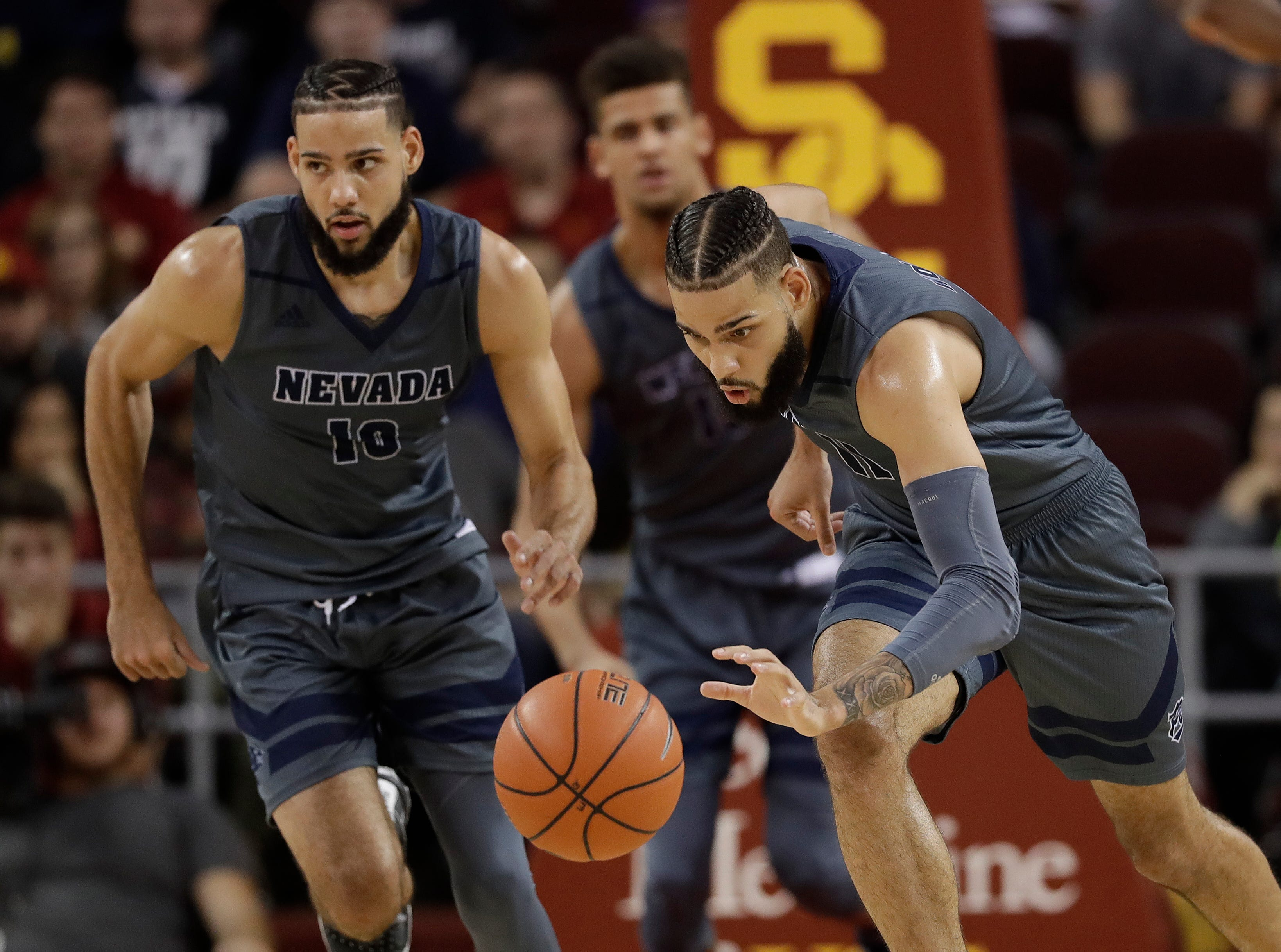 FILE - In this Dec. 1, 2018, file photo, Nevada forward Cody Martin, right, dribbles downcourt as his twin brother Caleb Martin, left, trails during the second half of an NCAA college basketball game against Southern California in Los Angeles. Florida's Jalen Hudson and the Martins will share the court in the opening round of the NCAA Tournament in Des Moines, Iowa. (AP Photo/Marcio Jose Sanchez, File)