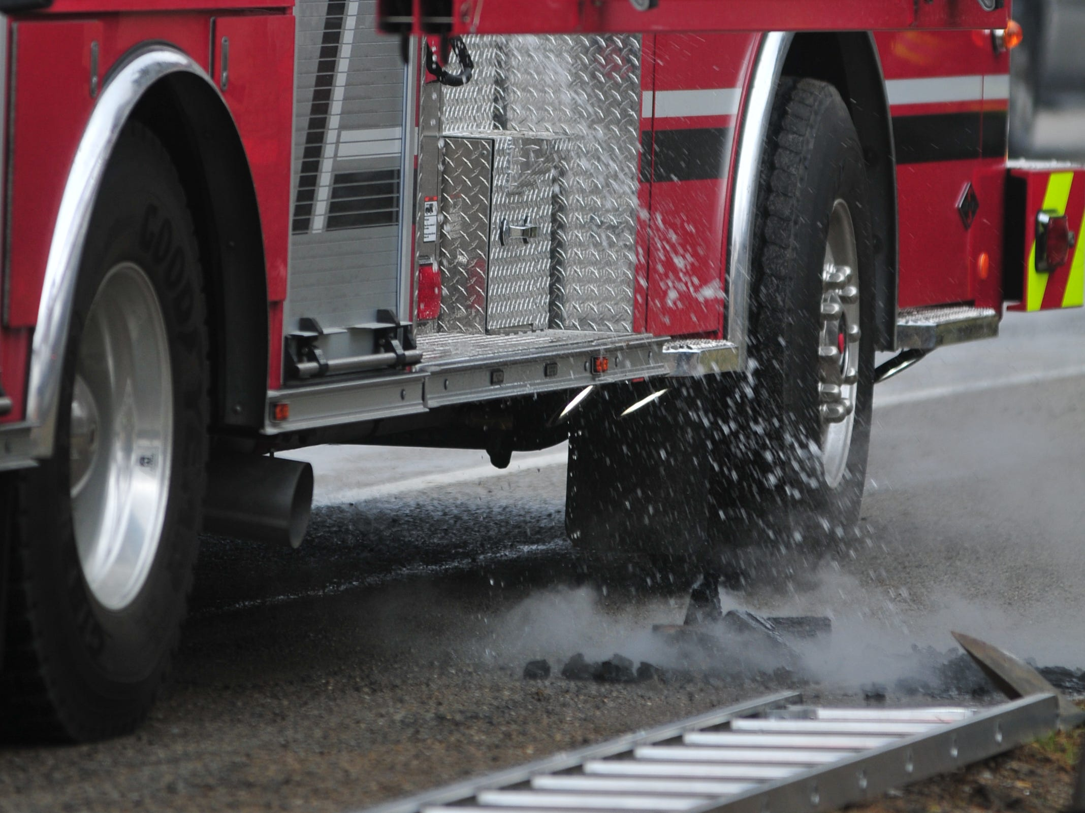 Water sprays from a fire truck onto the smoldering remnants of a fire inside a fireplace insert Thursday.