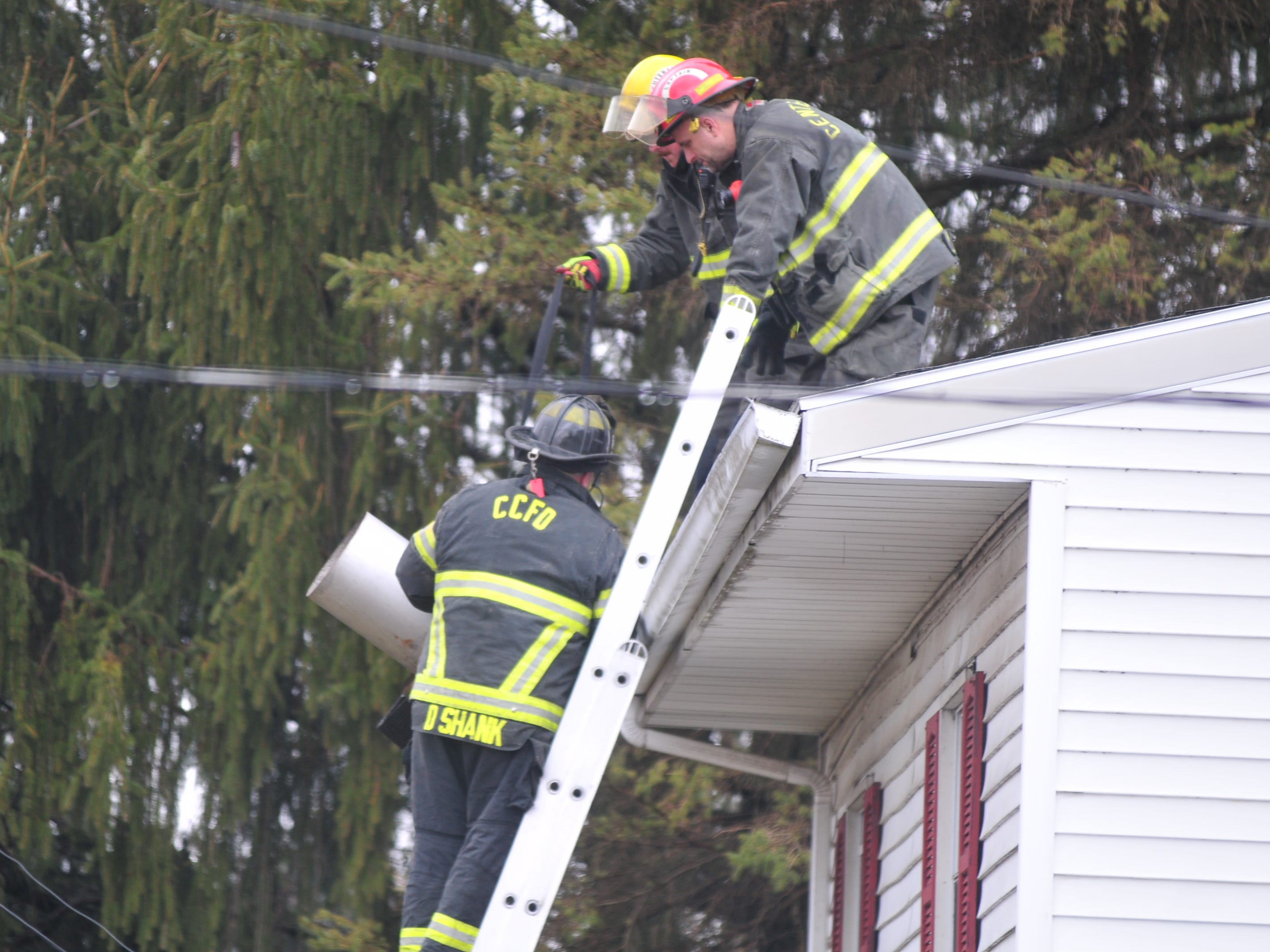 Firefighters work on the roof Thursday morning after responding to a chimney fire in the 6800 block of U.S. 40 West.