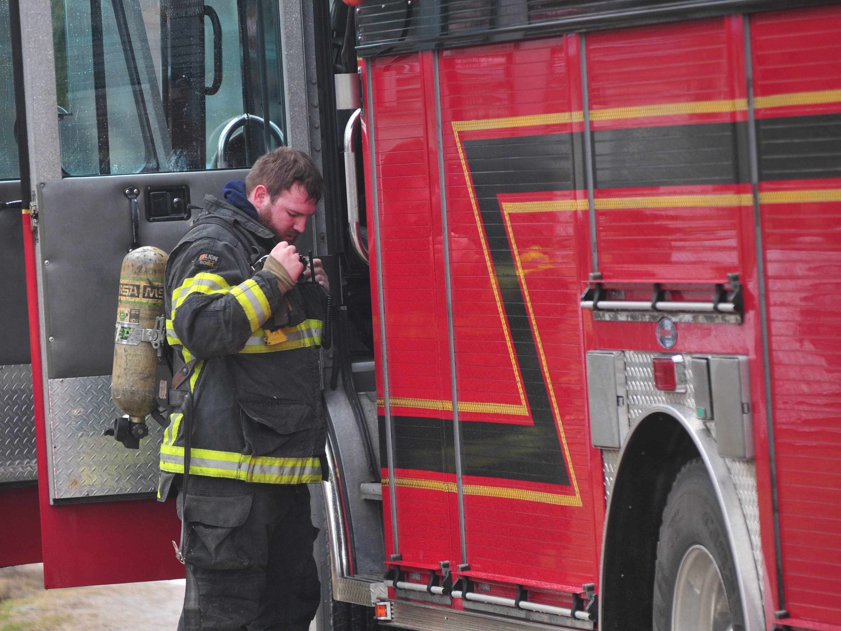 A firefighter removes his gear after working Thursday morning at a chimney fire in the 6800 block of U.S. 40 West.