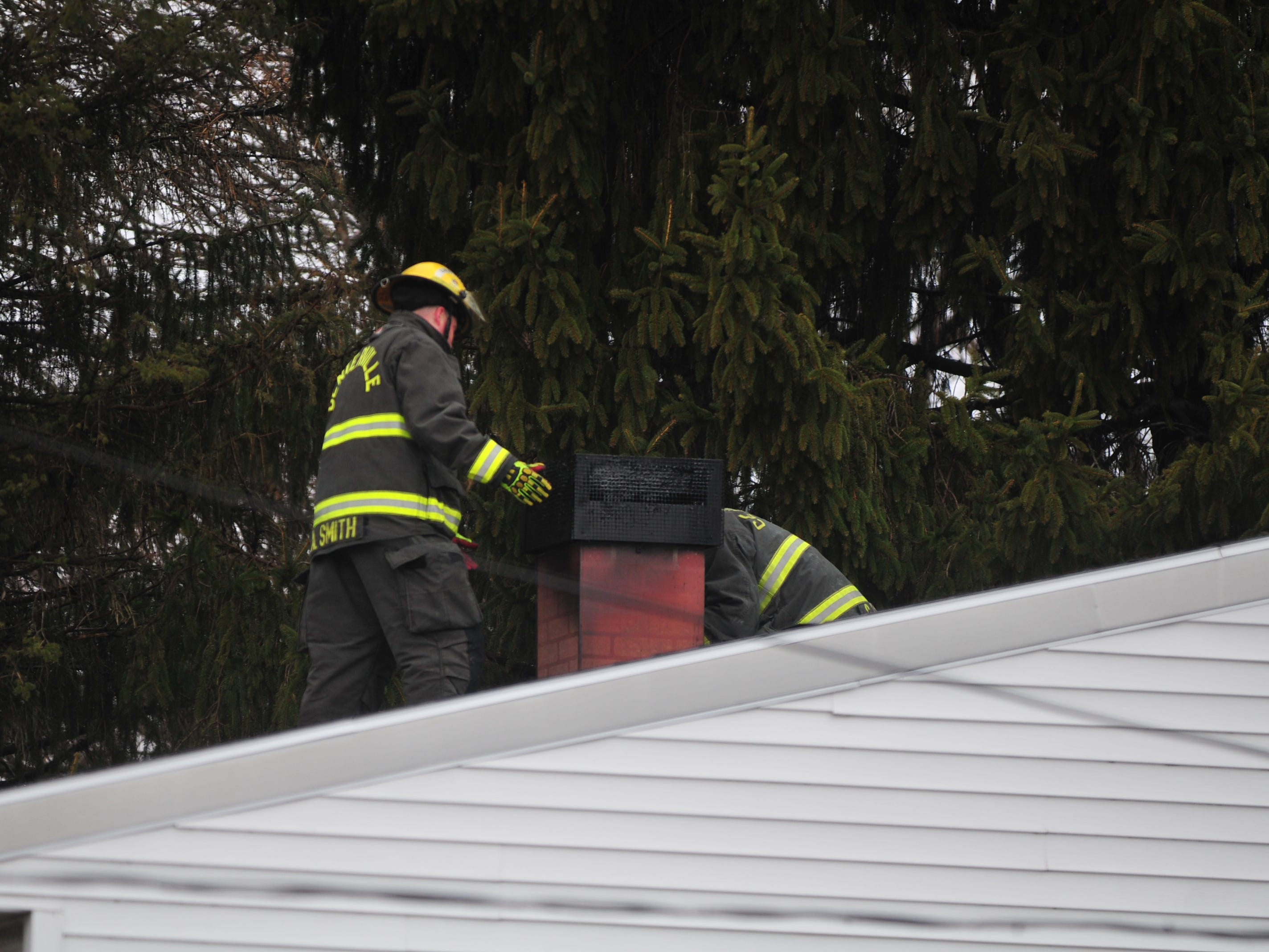 Firefighters work on the roof after responding to the 6800 block of U.S. 40 West for a chimney fire.