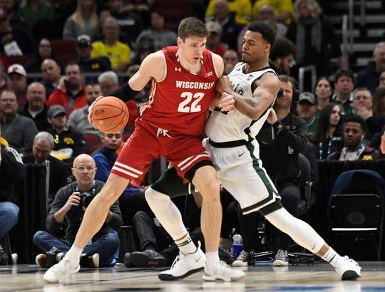 Mar 16, 2019; Chicago, IL, USA; Wisconsin Badgers forward Ethan Happ (22) controls the ball as Michigan State Spartans forward Xavier Tillman (23) defends during the second half in the Big Ten conference tournament at United Center. Mandatory Credit: David Banks-USA TODAY Sports