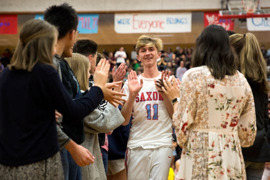 Saxons' Jacob Schnell (11) high-fives classmates as he's introduced in the starting lineup before an assembly and unified basketball game at South Salem High School in Salem on March 20, 2019.