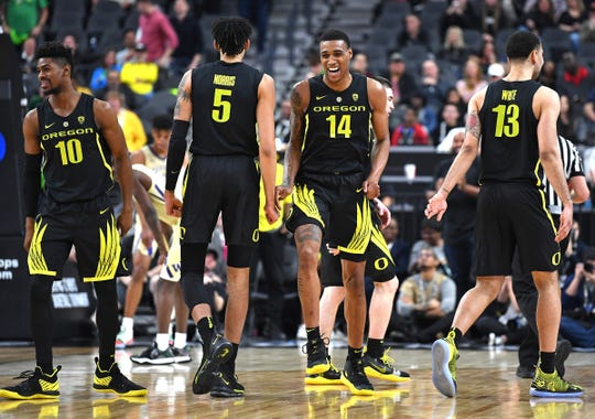 Mar 16, 2019; Las Vegas, NV, United States; Oregon Ducks forward Kenny Wooten (14) reacts as he walks up court with guard Victor Bailey Jr. (10) and forward Miles Norris (5), and forward Paul White (13) during the second half of the Pac-12 conference tournament final against the Washington Huskies at T-Mobile Arena. Mandatory Credit: Stephen R. Sylvanie-USA TODAY Sports
