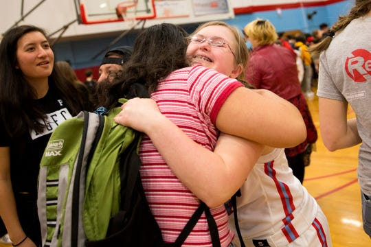 Saxons' Maddie Kelley hugs a friend after participating in an assembly and unified basketball game at South Salem High School in Salem on March 20, 2019.