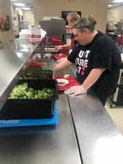 Heidi Bilben serves lunch at Fred Assam Elementary on Thursday, March 21 in Brandon.