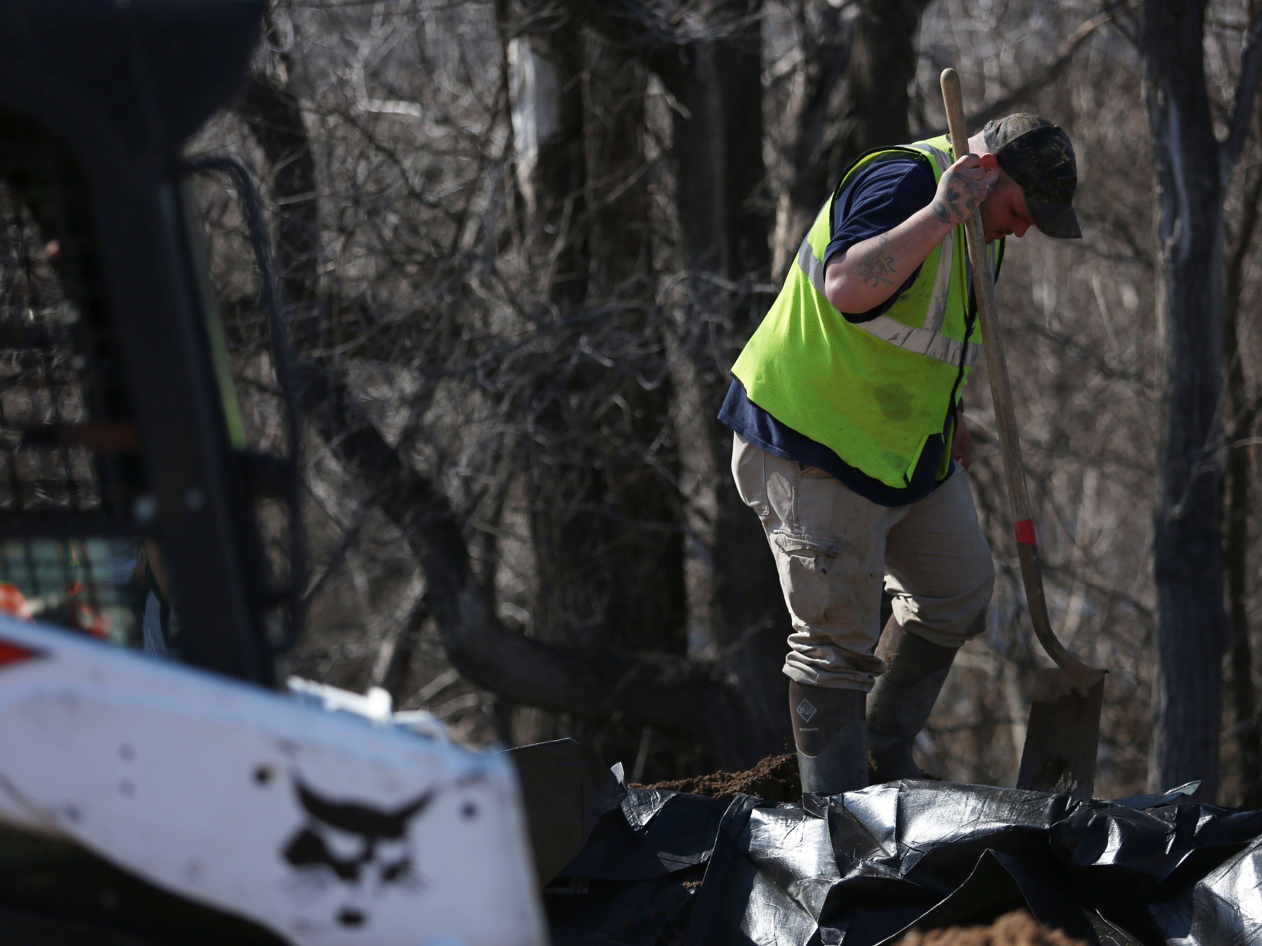 Cody Hilligas, with First Rate Excavate Labor, packs down sand inside trap bags along the Big Sioux River and Tomar Park March 21, 2019. The City of Sioux Falls installed a trap bag system near the Lotta Street and Minnesota Avenue residential area in hopes of preventing flooding early next week.