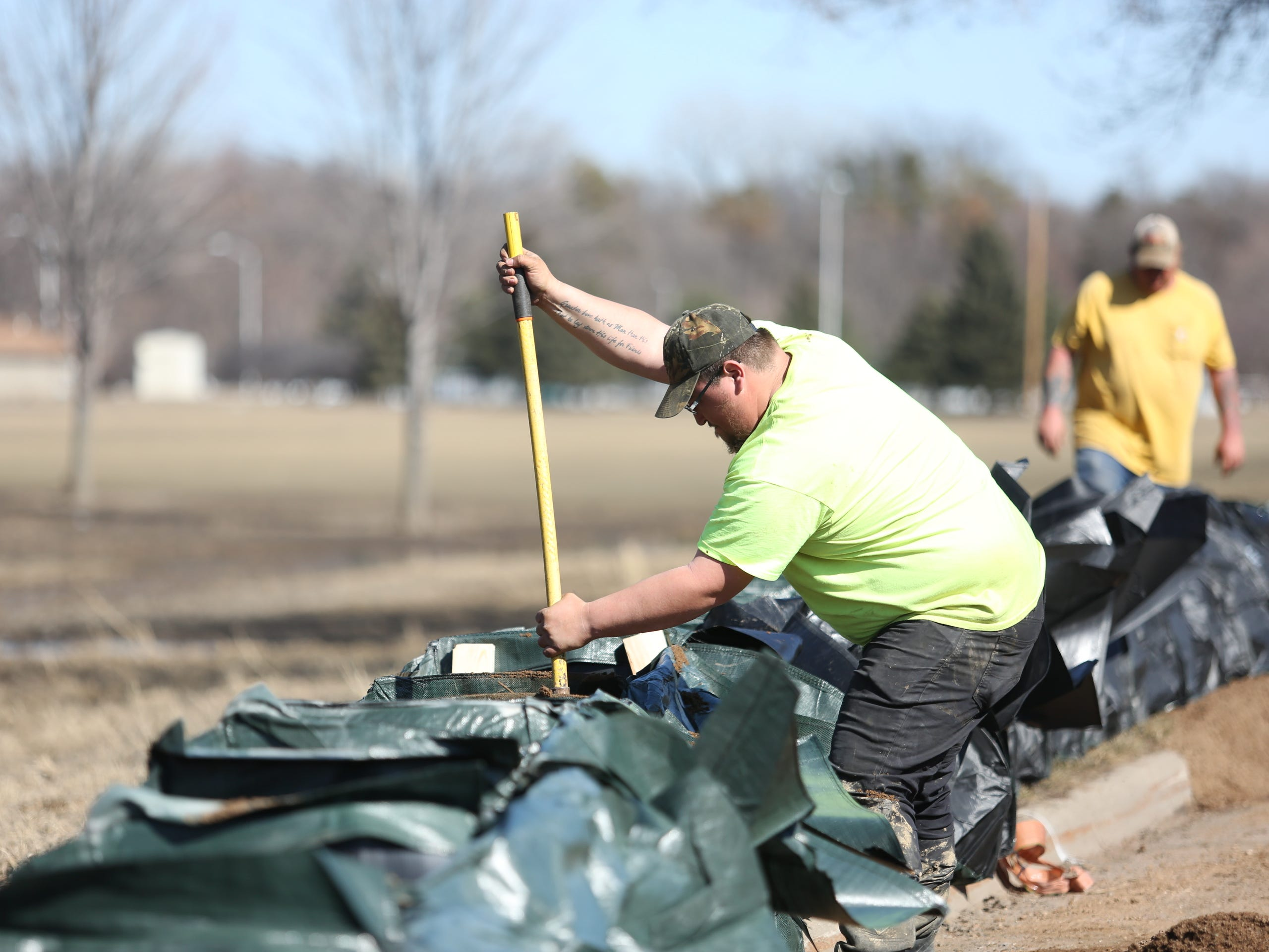 Tom Clark, with First Rate Excavate Labor, packs down sand inside trap bags along the Big Sioux River and Tomar Park March 21, 2019. The City of Sioux Falls installed a trap bag system near the Lotta Street and Minnesota Avenue residential area in hopes of preventing flooding early next week.