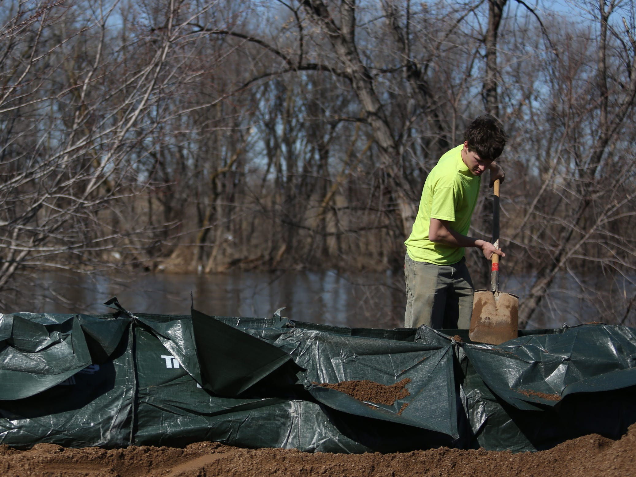 Allan-mark Iva, with First Rate Excavate Labor, packs down sand inside trap bags along the Big Sioux River and Tomar Park March 21, 2019. The City of Sioux Falls installed a trap bag system near the Lotta Street and Minnesota Avenue residential area in hopes of preventing flooding early next week.