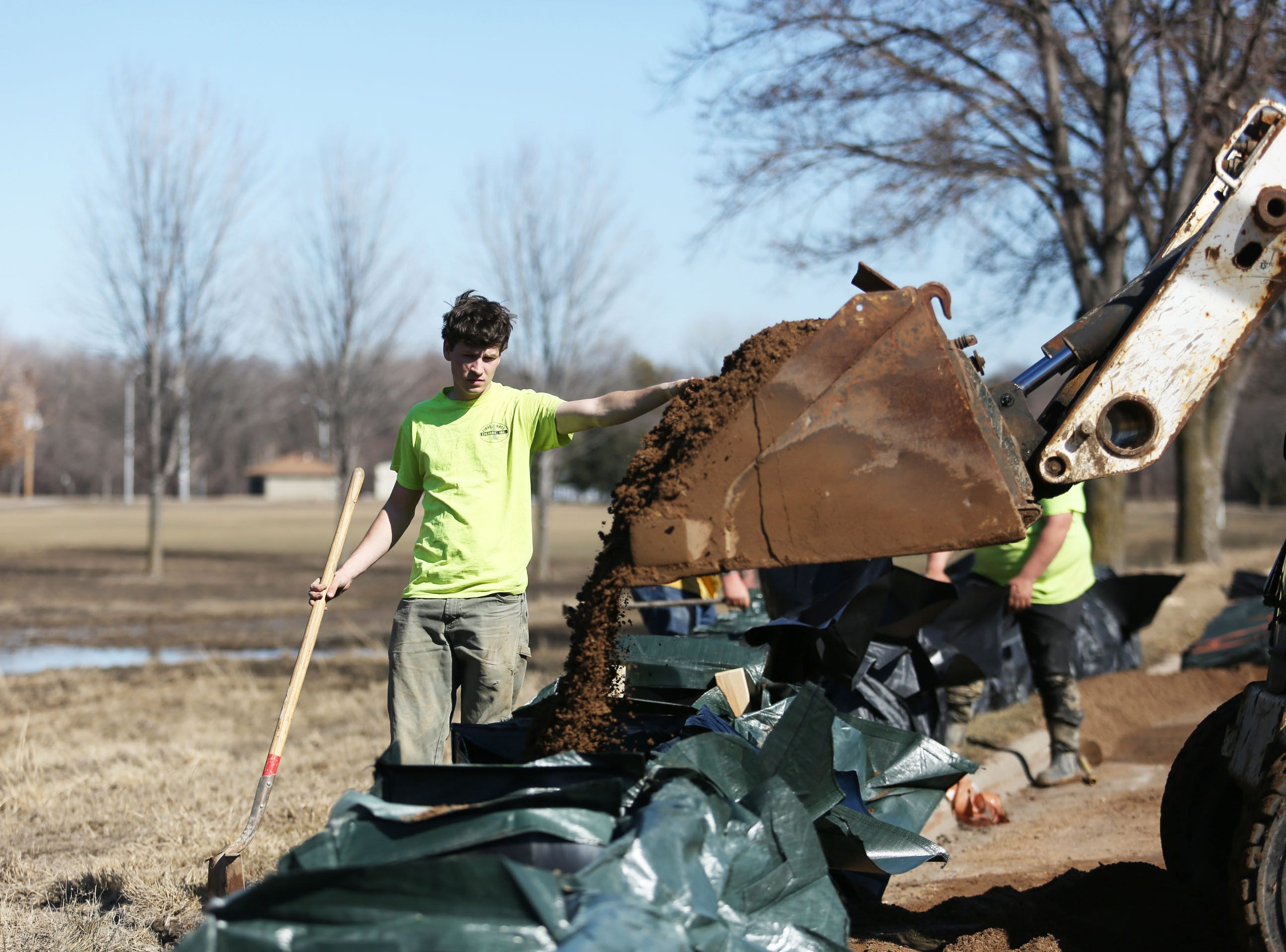 Allan-mark Iva, with First Rate Excavate Labor, helps fill trap bags along the Big Sioux River and Tomar Park March 21, 2019. The City of Sioux Falls installed a trap bag system near the Lotta Street and Minnesota Avenue residential area in hopes of preventing flooding early next week.