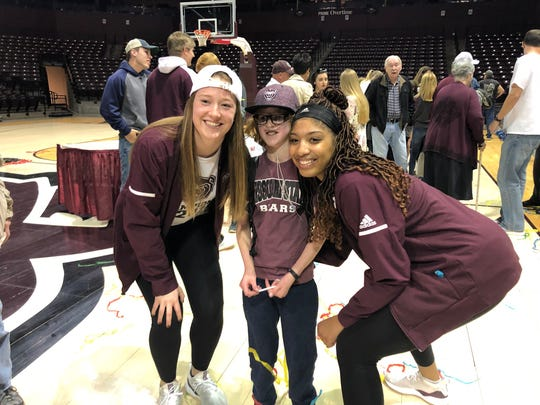 Elise Drennan smiles for a photo with sophomore Abby Hipp and junior Shameka Ealy.