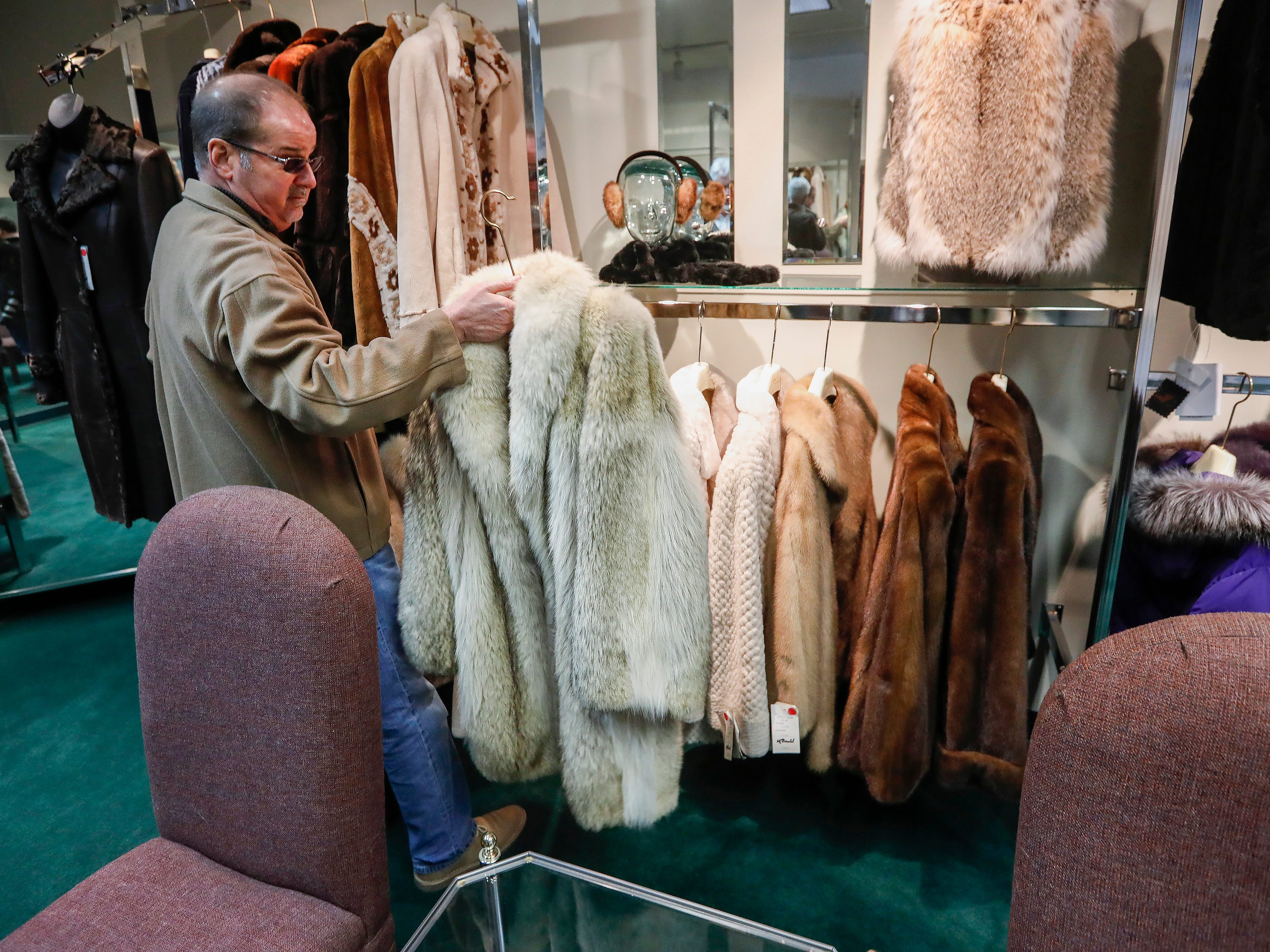 Jeff Latimer, owner of McDaniel Furs, shows off a jacket that he sells at his store which is located at 901 S. Glenstone Ave.