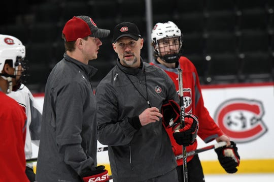 St. Cloud State head coach Brett Larson talks to assistant coach Nick Oliver on Thursday during practice at the Xcel Energy Center in St. Paul.