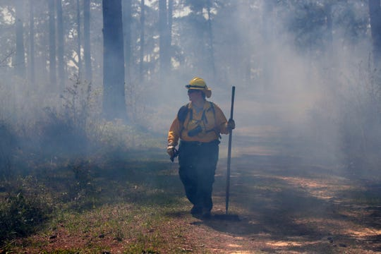 Colleen Bowers, a firefighter from North Carolina, walks through the smoke of a controlled burn Thursday, March 21, 2019. Tall Timbers in Tallahassee, Fla. hosts Women-in-Fire Prescribed Fire Training Exchange (WTREX) which engages women and men  working to advance their leadership in wildland fire management.