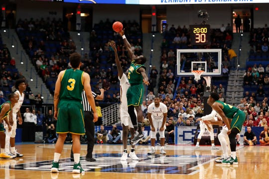 Mar 21, 2019; Hartford, CT, USA; Vermont Catamounts forward Samuel Dingba (5) reaches over Florida State Seminoles center Christ Koumadje (21) for the ball in the opening tip off in the first round of the 2019 NCAA Tournament at XL Center. Mandatory Credit: David Butler II-USA TODAY Sports