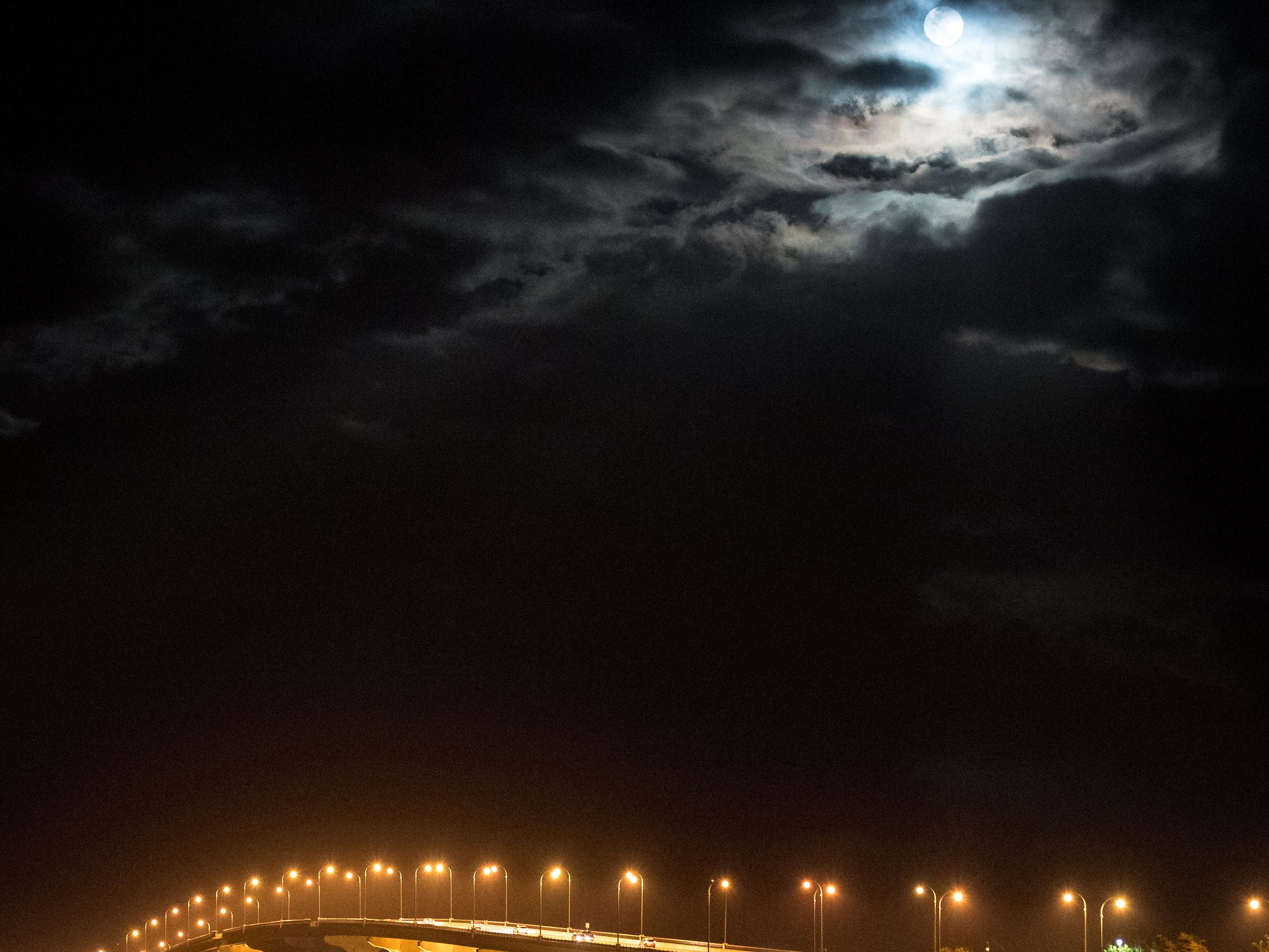 """The last supermoon of 2019, the """"super worm equinox moon,"""" is seen over the Jensen Beach Causeway through an overcast night sky on the vernal equinox Wednesday, March 20, 2019, in Jensen Beach. The next supermoon will not occur until March 2020."""