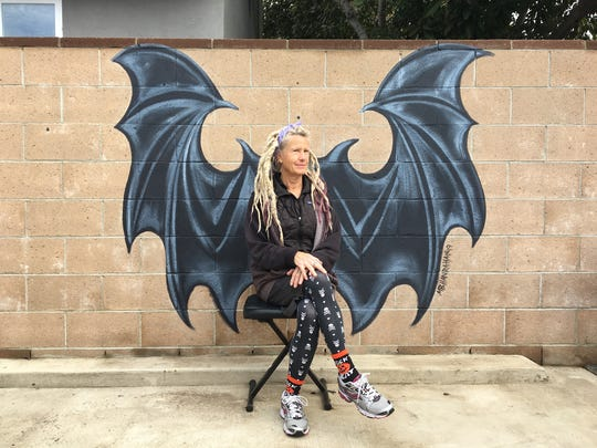 Ventura artist MB Hanrahan poses in front of the bat wings she painted on a backyard wall at the Ventura home of baker Deb Dawson. Bakewell House patrons are invited to strike poses of their own when the pop-up bakery is in operation on Friday mornings.