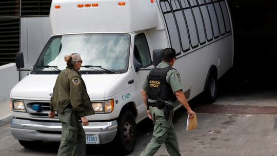 In this Tuesday photo, a van carrying asylum seekers from the border is escorted by security personnel as it arrives to immigration court in San Diego. Scheduling glitches led an immigration judge to deny the Trump administration's request to order four Central American migrants deported because they failed to show for initial hearings Wednesday.