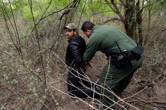 In this March 14 photo, a Border Patrol agent apprehends a person suspected of having entered the U.S. illegally near McAllen, Texas. While many adults crossing the border on their own in South Texas try to flee agents, most migrant parents and children wait to surrender so they can be processed and released into the United States.