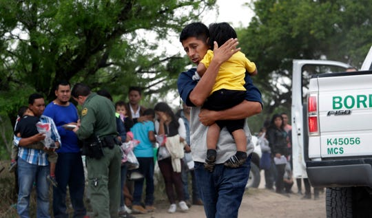In this March 14 photo, Jose Fermin Gonzalez Cruz holds his son, William Josue Gonzales Garcia as they wait with other families who crossed the nearby U.S.-Mexico border near McAllen, Texas, for Border Patrol agents to check names and documents. Immigration authorities say they expect the ongoing surge of Central American families crossing the border to multiply in the coming months.