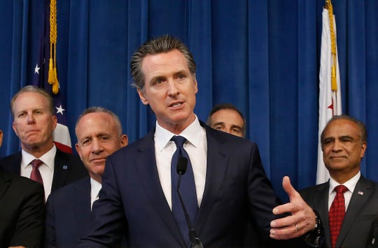 Gov. Gavin Newsom, center, discusses the homeless problem facing California after a meeting with the mayors of some of the state's largest cities held at the governor's office on Wednesday in Sacramento.