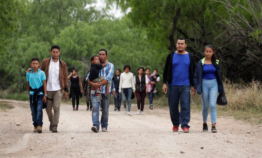 In this March 14 photo, a group of migrant families walk from the Rio Grande, the river separating the U.S. and Mexico in Texas, near McAllen, Texas. The migrants said they crossed the river in an inflatable raft and were hoping to be apprehended by the Border Patrol so they could be processed and released.