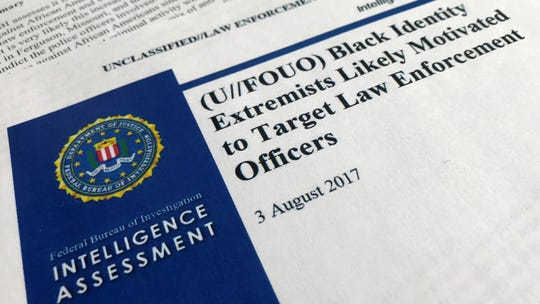 """In this Nov. 17, 2017, file photo, the cover page of a FBI report on the rise of black """"extremists"""" is photographed in Washington."""