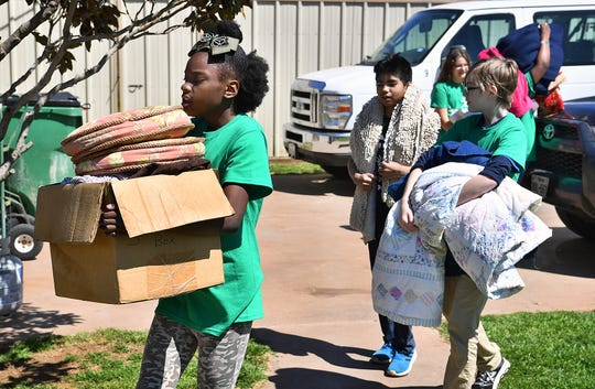 A group of junior high students with Camp Fire USA haul in donated blankets at a dog shelter in Petrolia as part of Absolutely Incredible Kids Day Thursday.