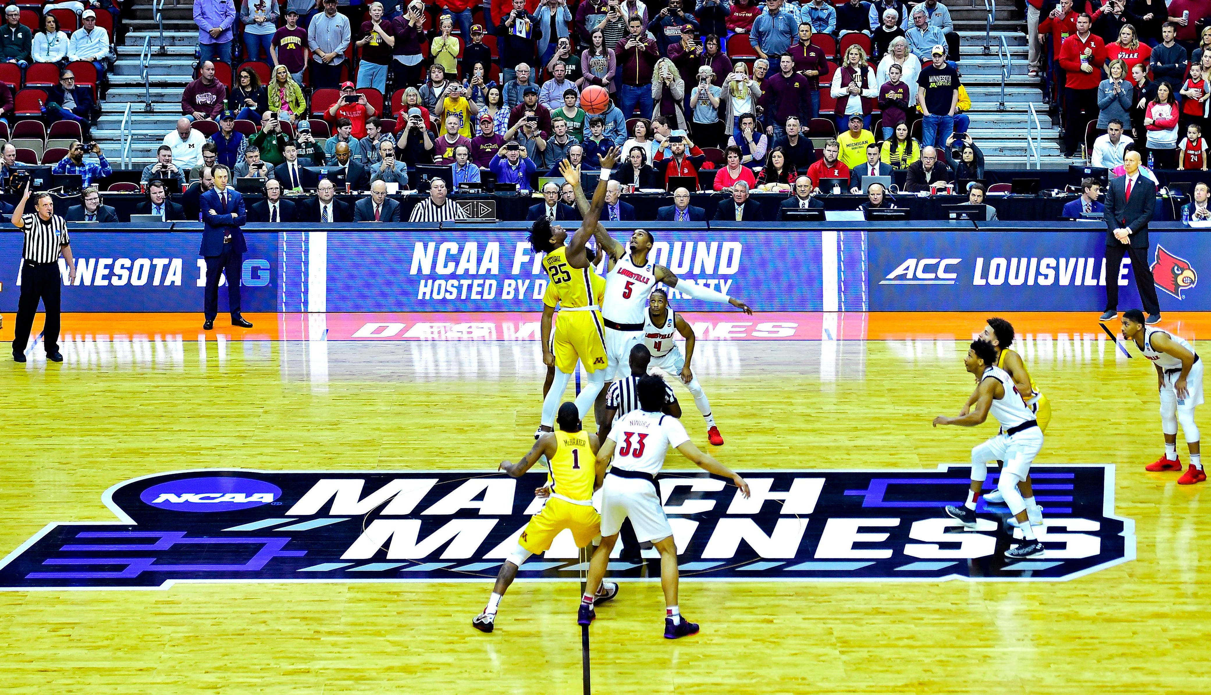 Minnesota center Daniel Oturu, left,  (25) and Louisville center Malik Williams go for the opening tip in the first round of the 2019 NCAA tournament.