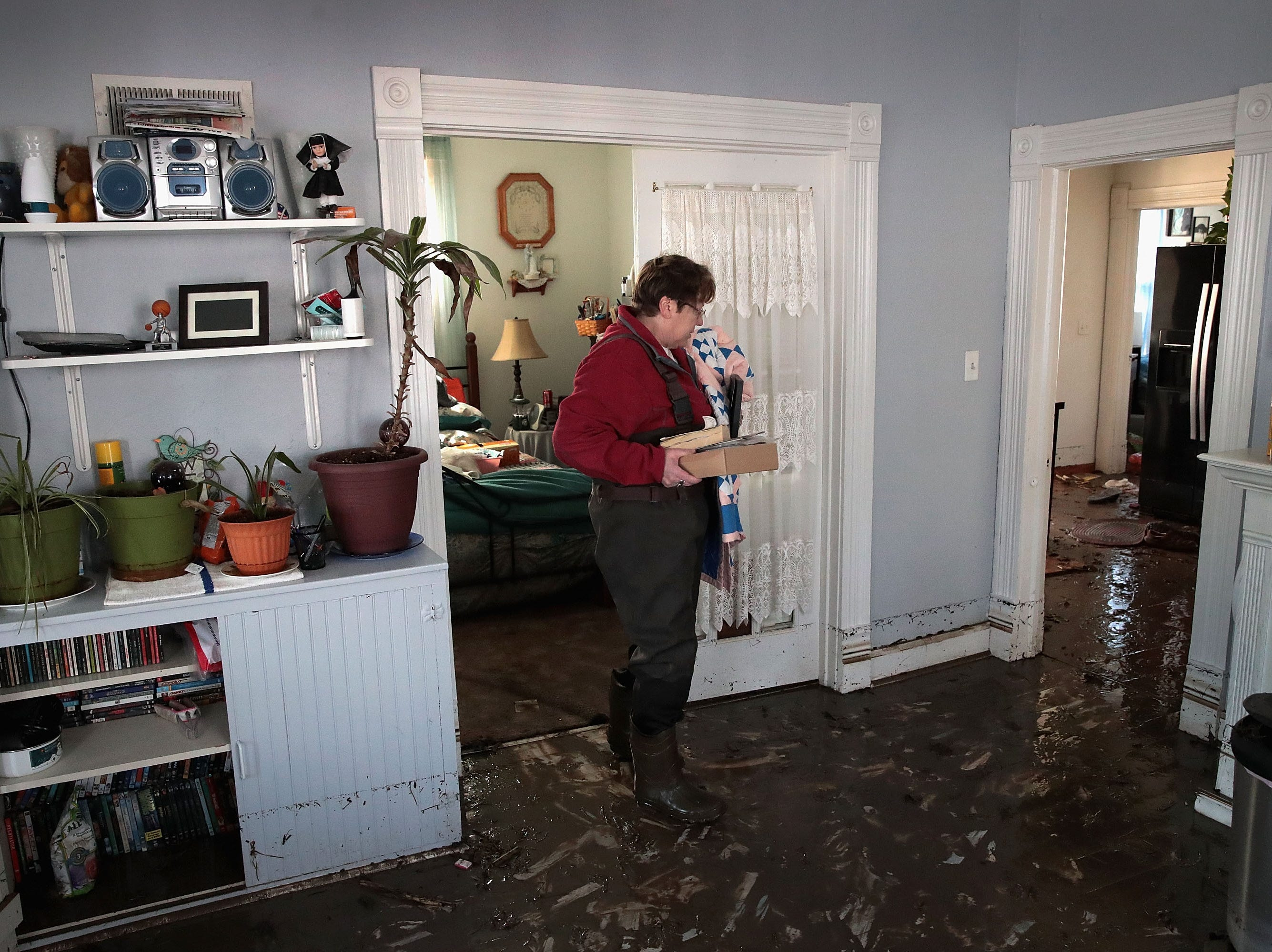 Kathy Drummond recovers items from her flooded home on March 20, 2019 in Hamburg, Iowa.