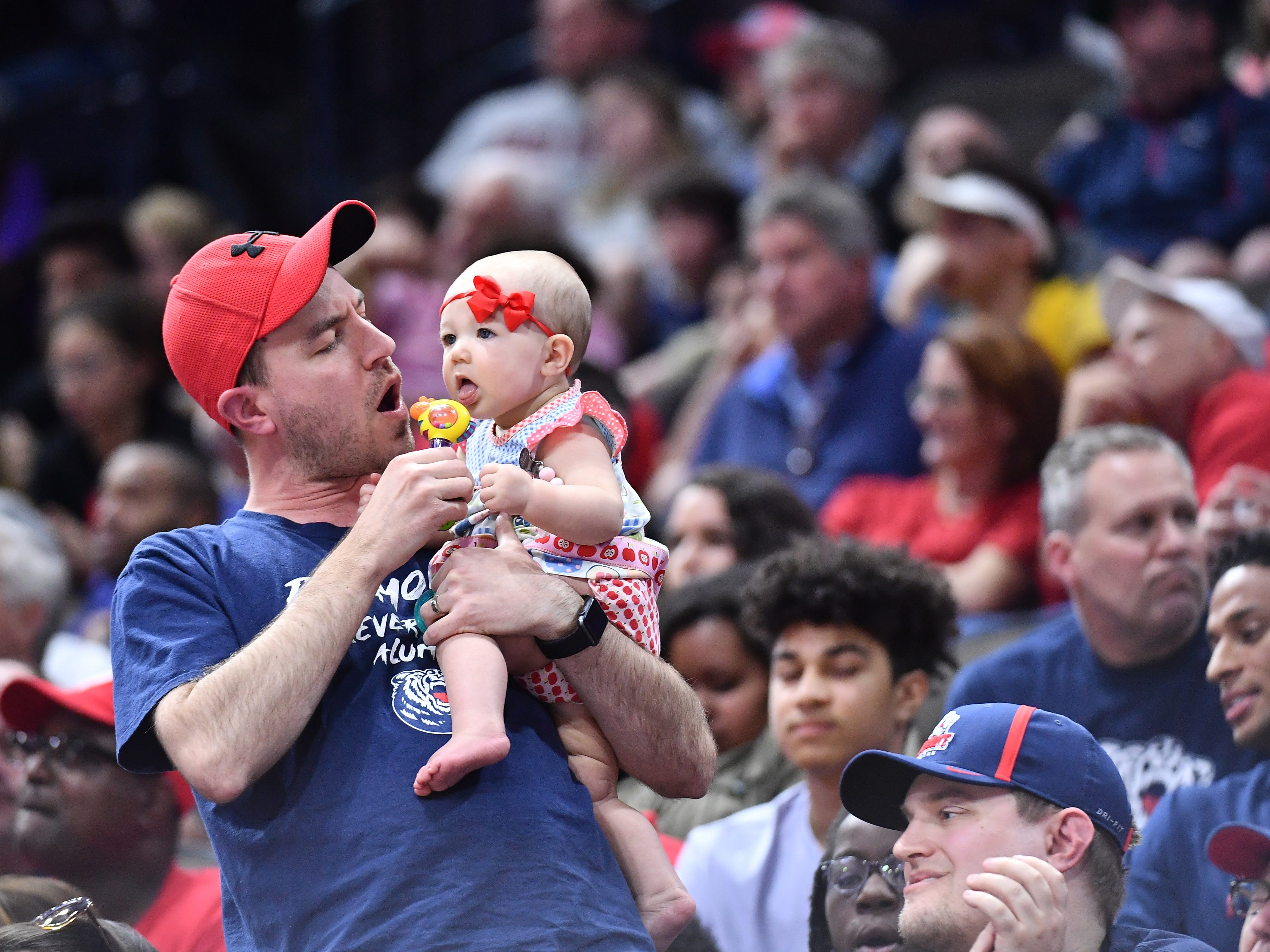 First round: A father-baby duo sing along during the game between Maryland and Belmont.