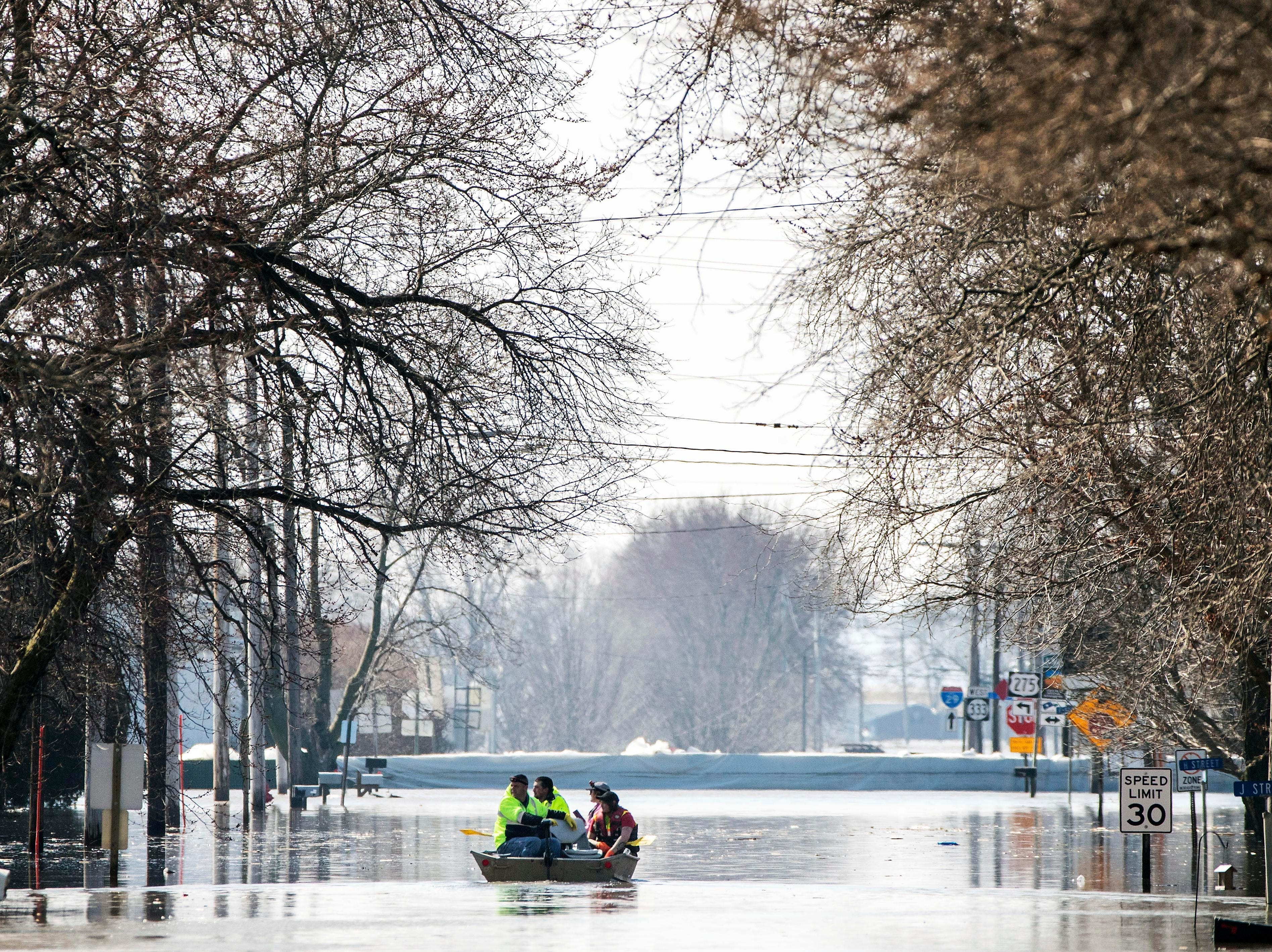 People in a boat float down floodwaters that cover Washington Street on March 20, 2019, in Hamburg, Iowa.