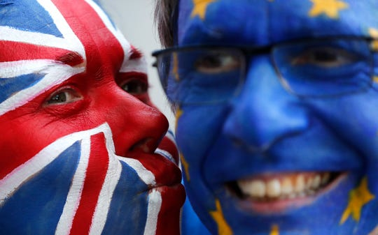 Activists pose with their faces painted in the British and EU colors during an anti-Brexit campaign stunt outside EU headquarters in Brussels, Belgium, on March 21, 2019.