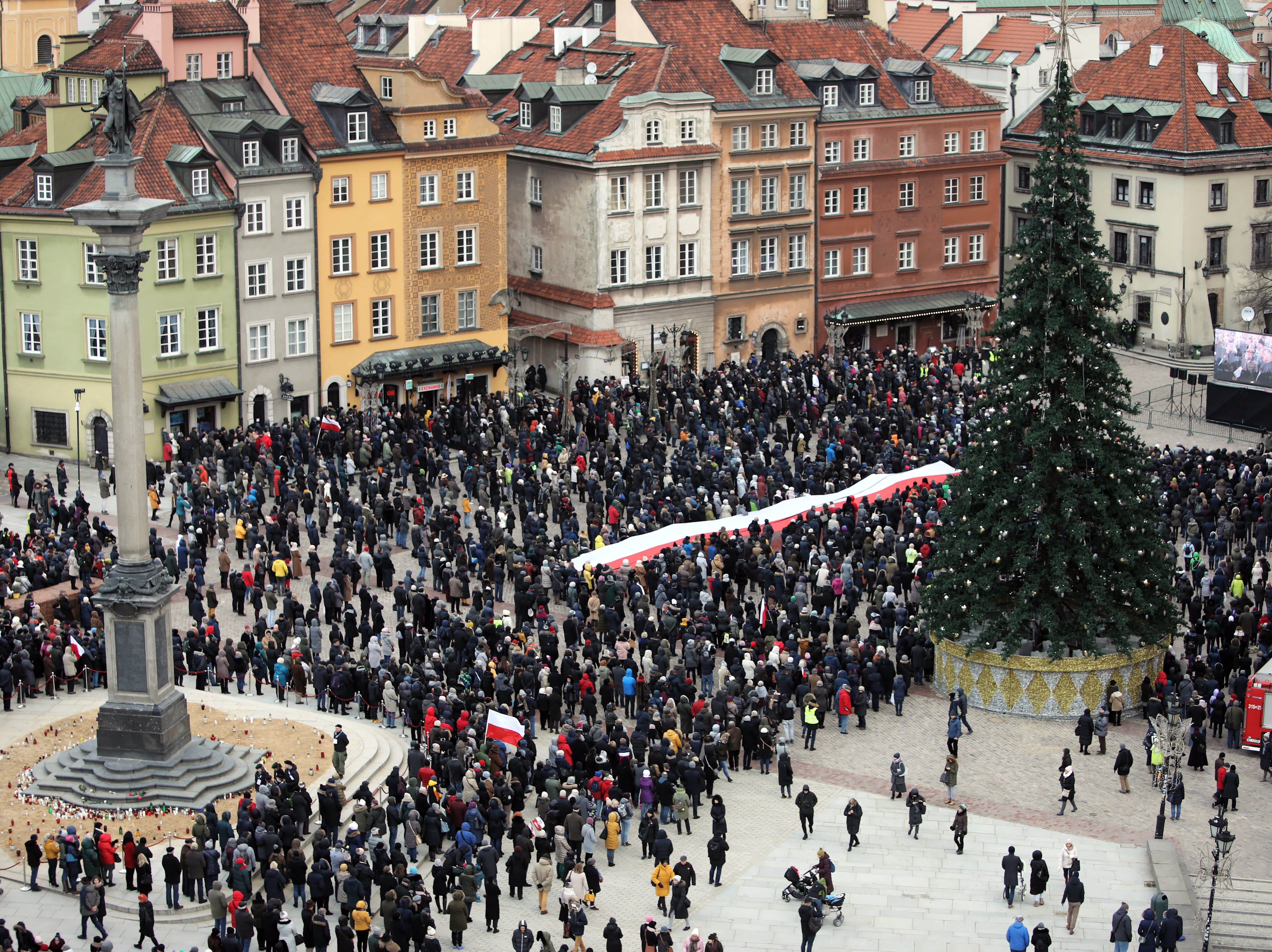 epa07299566 People gather on the Castle Square to watch on big screens a funeral service of the late Gdansk Mayor Pawel Adamowicz, in Warsaw, Poland, 19 January 2019. On 13 January evening Gdansk Mayor Pawel Adamowicz was stabbed by a recently released convicted criminal who rushed onto the stage during the Great Orchestra of Christmas Charity finale in Gdansk. Adamowicz died from his injuries on 14 January afternoon without regaining consciousness. Adamowicz will be laid to rest in Gdansk's St. Mary's Basilica.  EPA-EFE/LESZEK SZYMANSKI POLAND OUT