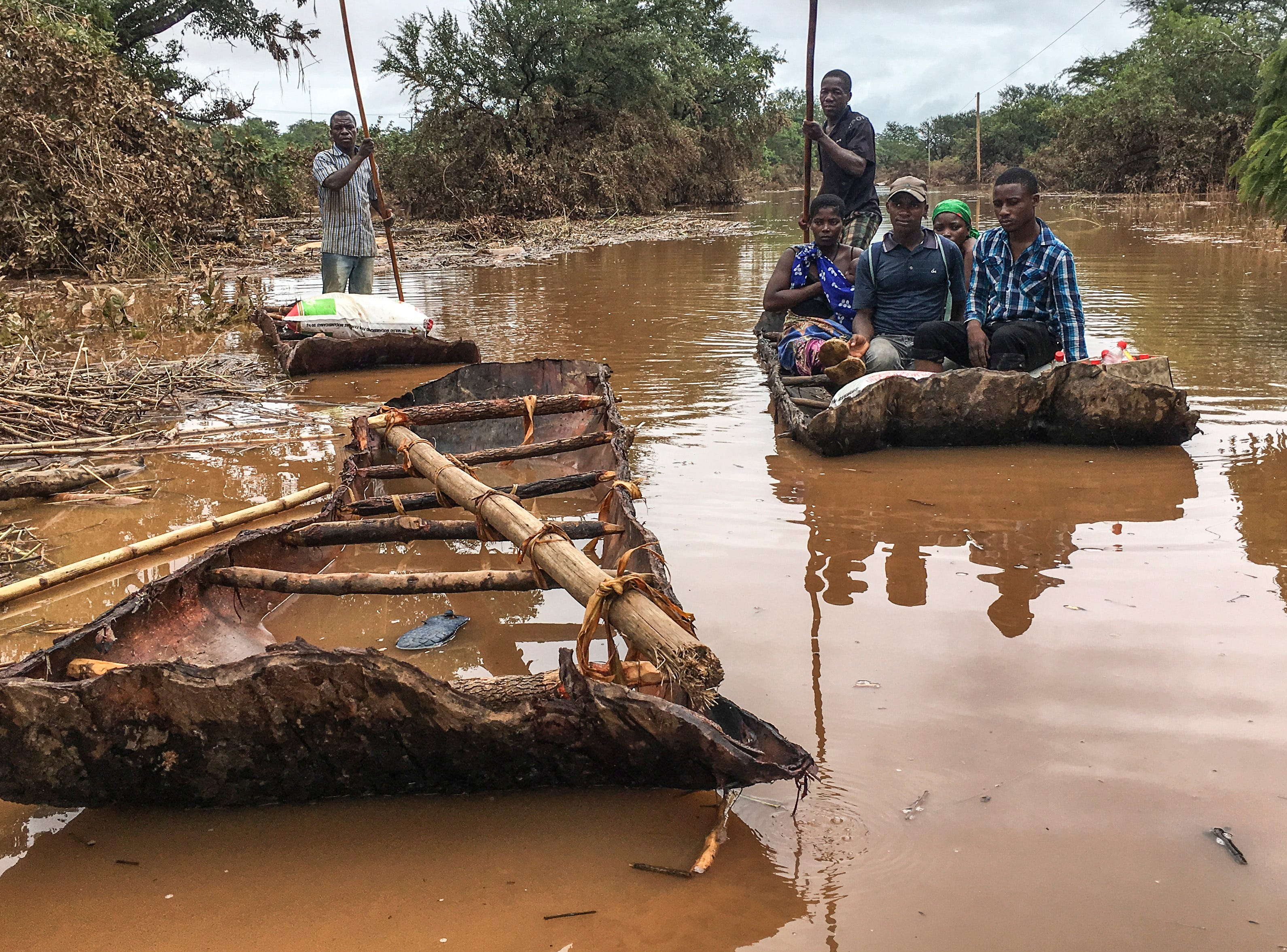 Civilians use makeshift boats to navigate flooded areas after Cyclone Idai tore through central Mozambique.