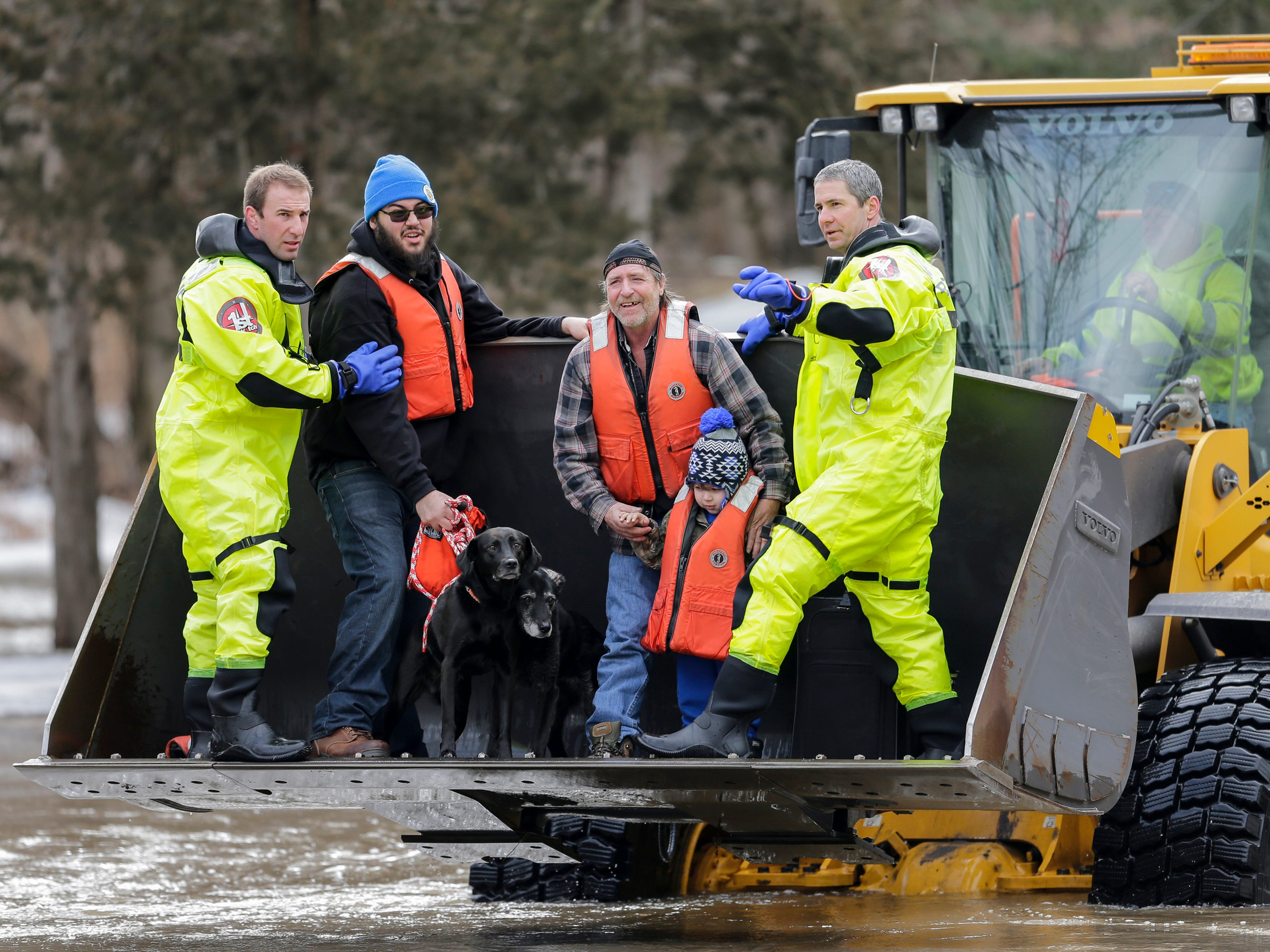 From left, Ethan Perez, Keith Pfeifer and Ean Pennell, 3, are evacuated from their residences in Manitowoc, Wis., by firefighters Kevin Fabian, left, and Garrett Grissom, right, after an ice jam on the Manitowoc River flooded the block Thursday, March 21, 2019.