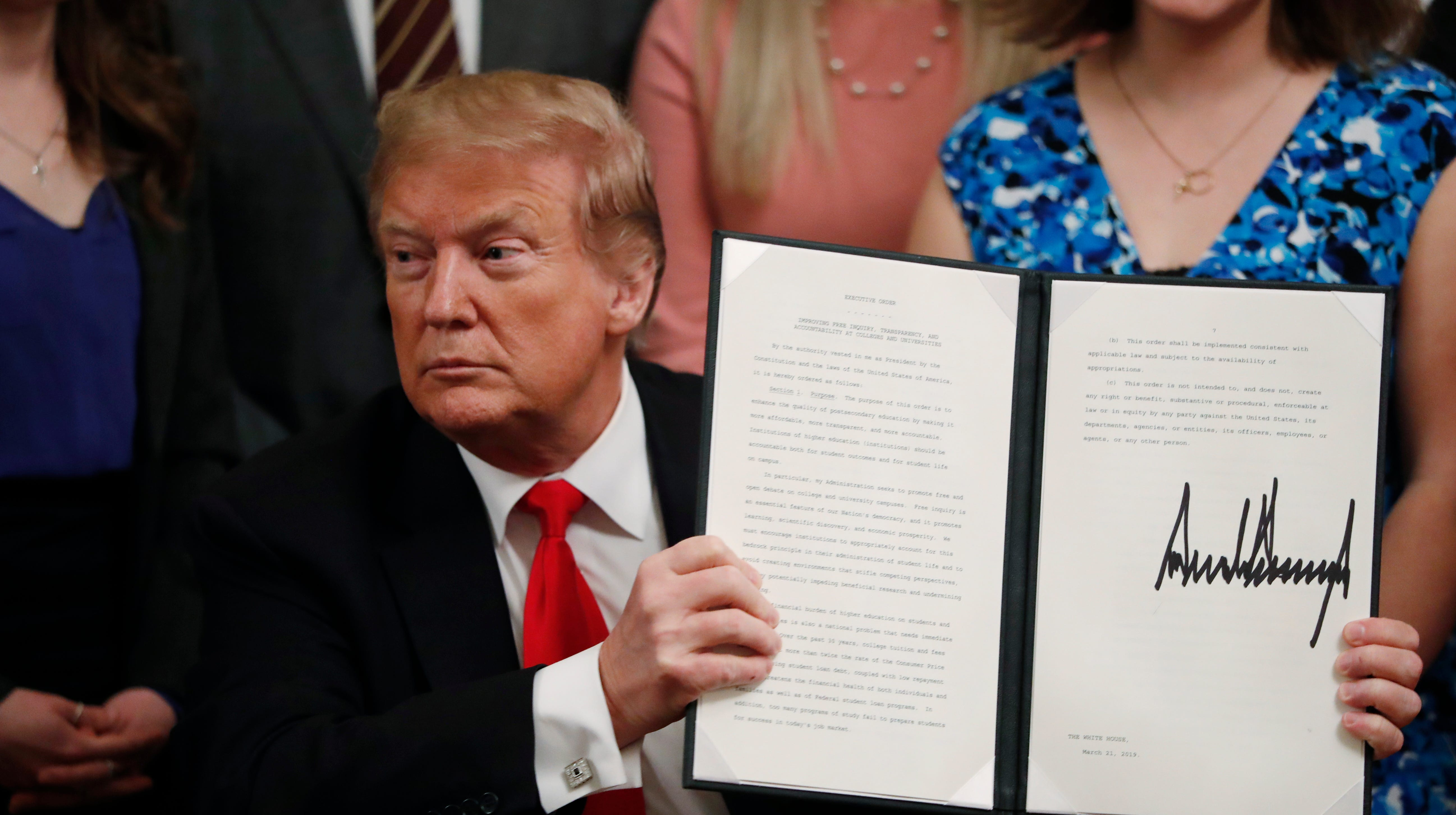 President Donald Trump holds up an executive order requiring colleges to certify that their policies support free speech as a condition of receiving federal research grants, after signing, Thursday March 21, 2019, in the East Room of the White House in Washington. (AP Photo/Jacquelyn Martin) ORG XMIT: DCJM209