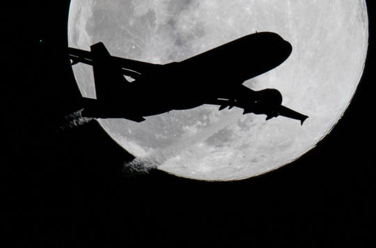 An airplane preparing to land at the airport in Frankfurt am Main, western Germany, silhouettes against the full moon on March 20, 2019; pictured in Offenbach, western Germany. (Photo by Boris Roessler / dpa / AFP) / Germany OUTBORIS ROESSLER/AFP/Getty Images ORIG FILE ID: 587261335