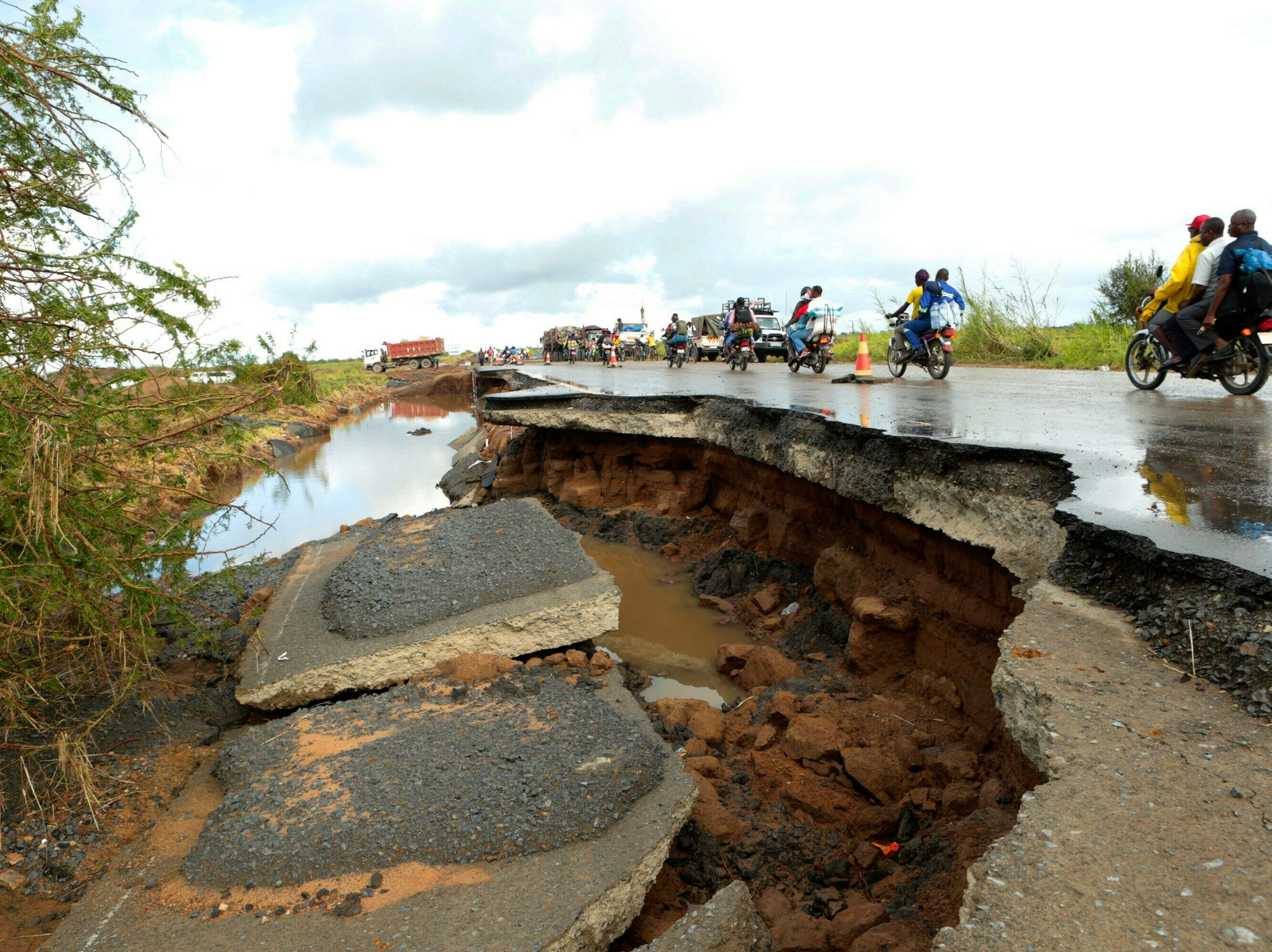 Motorcycles pass through a section of road damaged by Cyclone Idai near Beira, Mozambique on March 21, 2019.