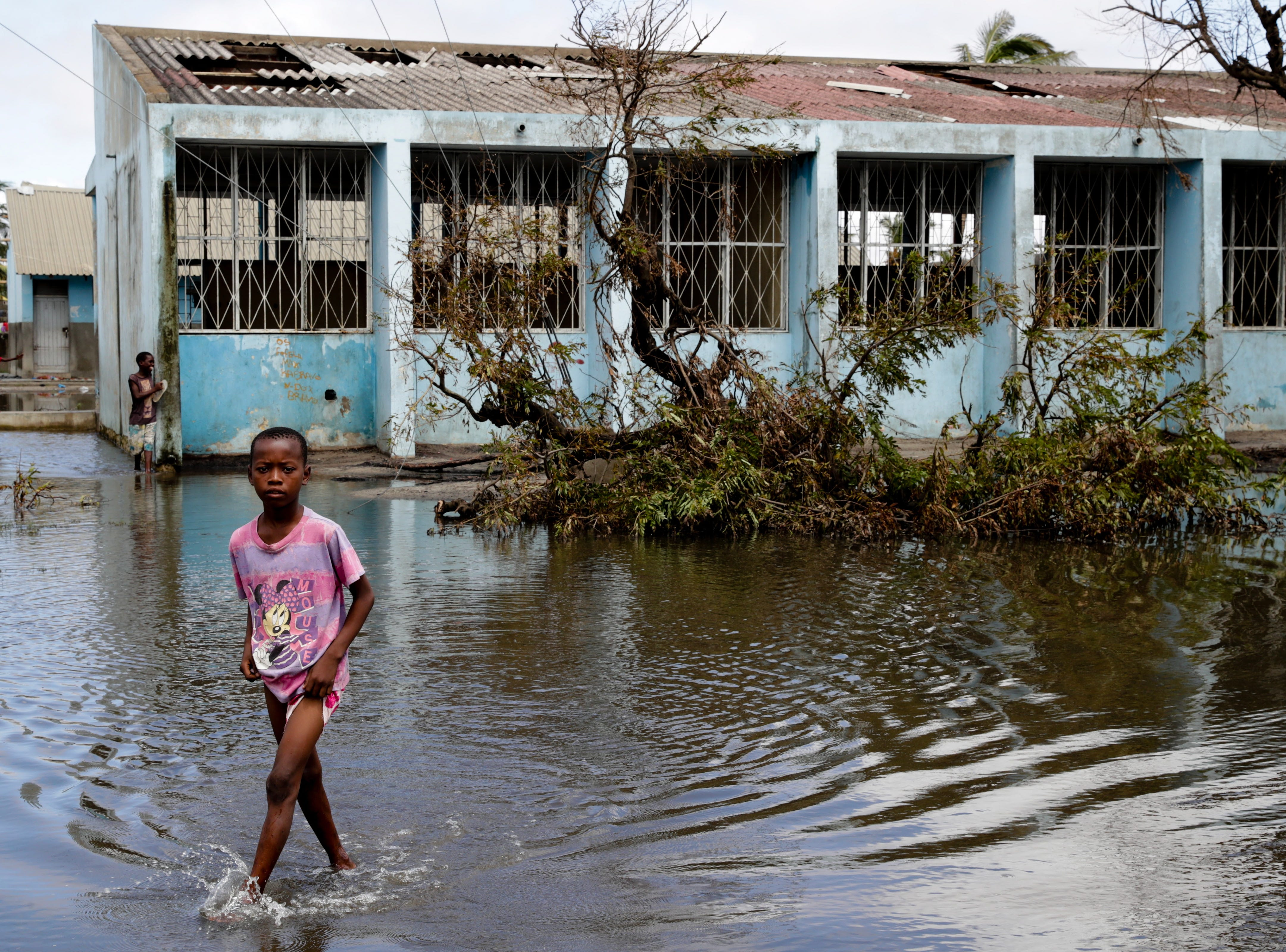 A child wades through floodwaters while waiting for drinkable water to be delivered by local authorities after a cut on the public supply of water after Cyclone Idai hit Beira City in central Mozambique.