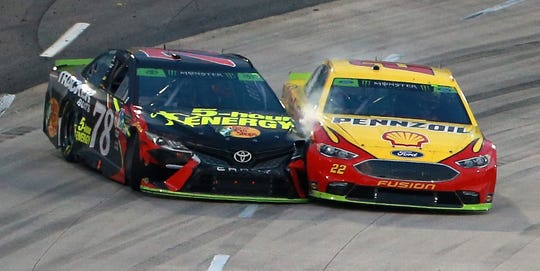 Joey Logano (right) and Martin Truex Jr. race out of Turn 4 at Martinsville Speedway in October.