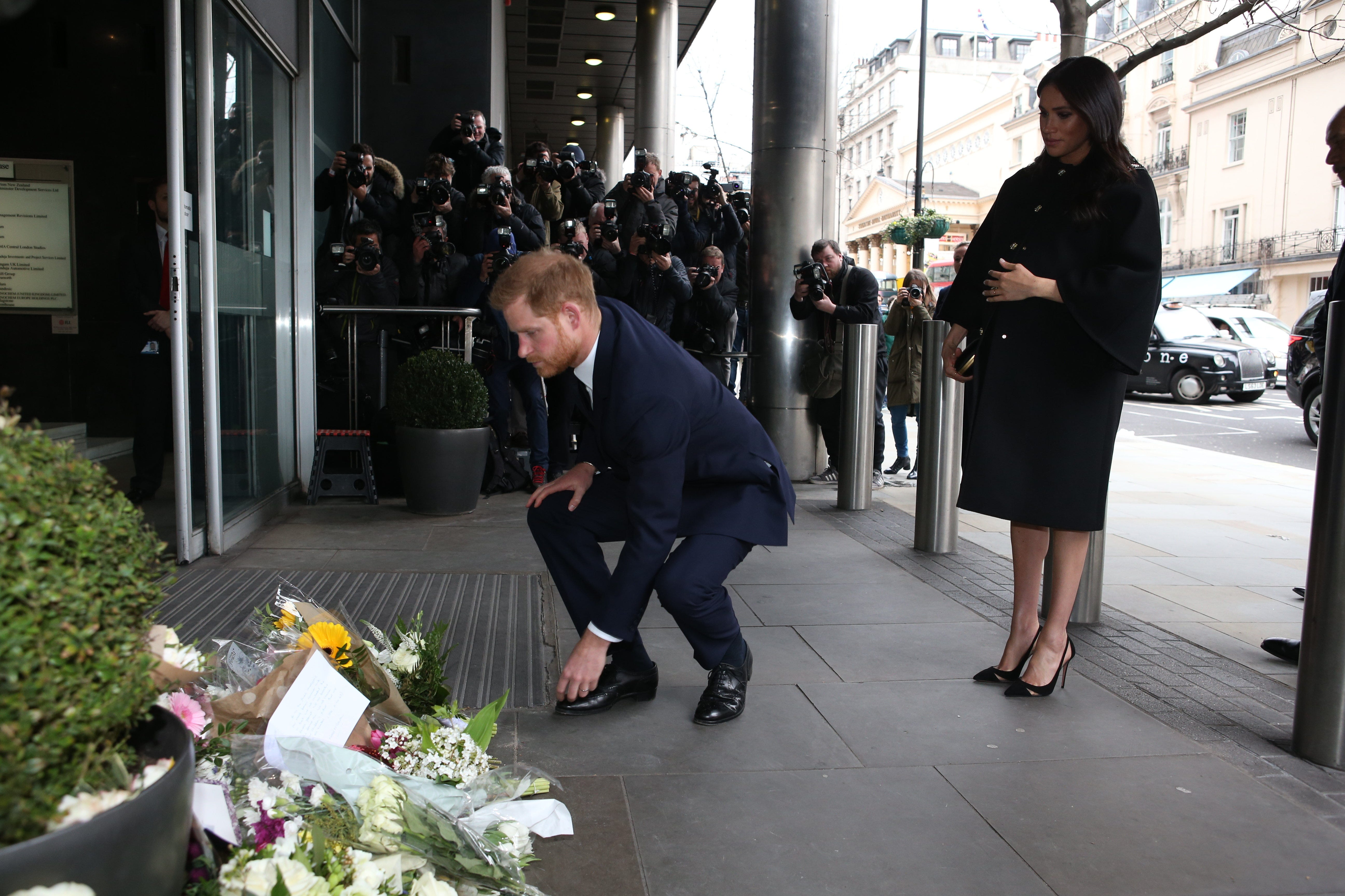 Duchess Meghan of Sussex and Prince Harry lay floral tributes at New Zealand House on March 19, 2019 in London, following the recent terror attack at mosques in Christchurch that killed 50 people.