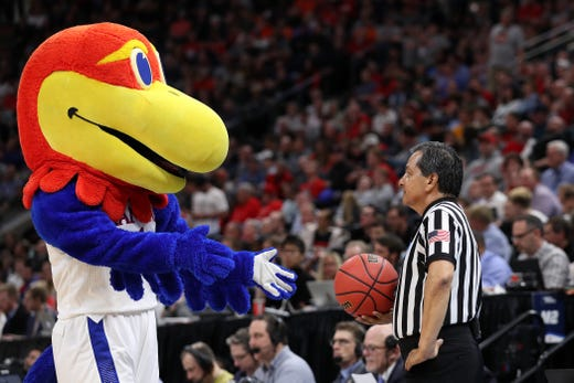 First round: The Kansas Jayhawks mascot interacts with a referee during the game against the Northeastern Huskies.