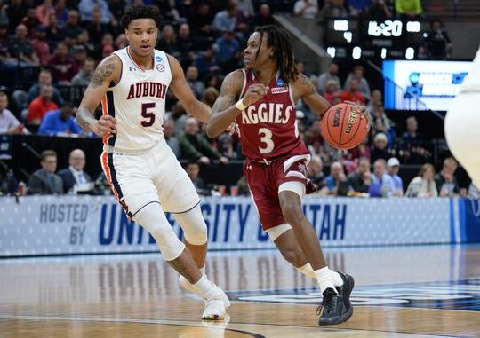 New Mexico State guard Terrell Brown drives around Auburn forward Chuma Okeke the first round of the 2019 NCAA tournament.