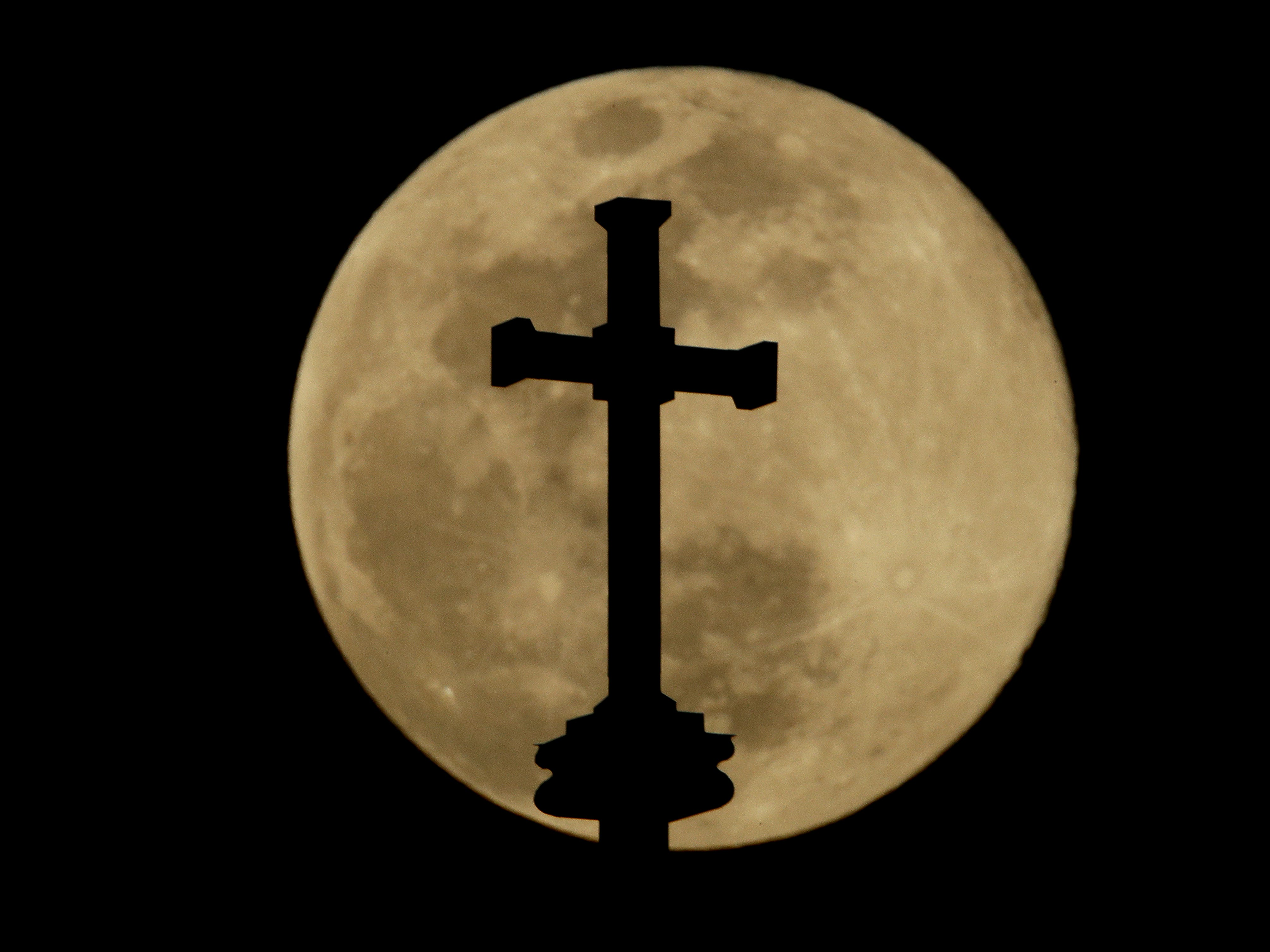 A cross on top of the Holy Family Cathedral is silhouetted against the rising full moon Wednesday, March 20, 2019, in Tulsa, Okla. (AP Photo/Charlie Riedel) ORG XMIT: KSCR101