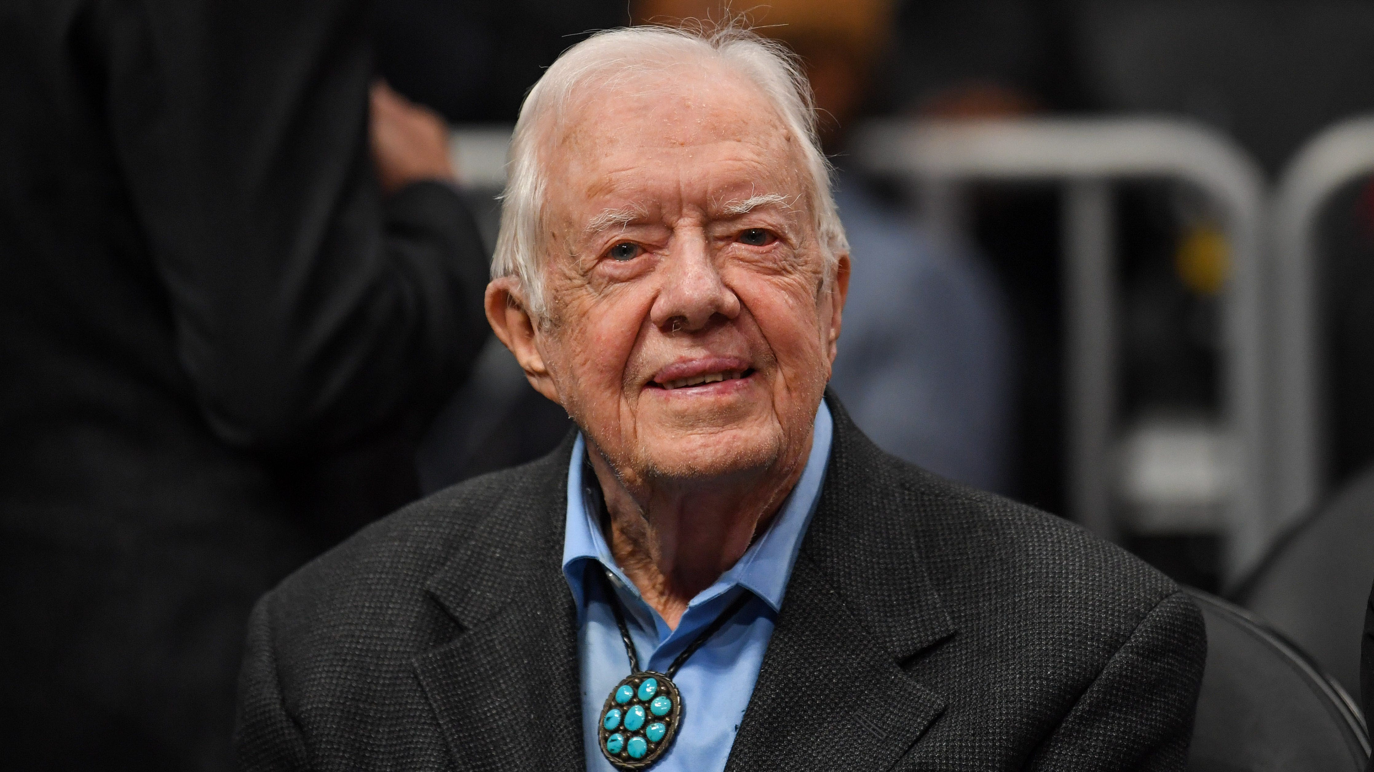 Former president Jimmy Carter shown at the game between the Atlanta Hawks and the New York Knicks at State Farm Arena