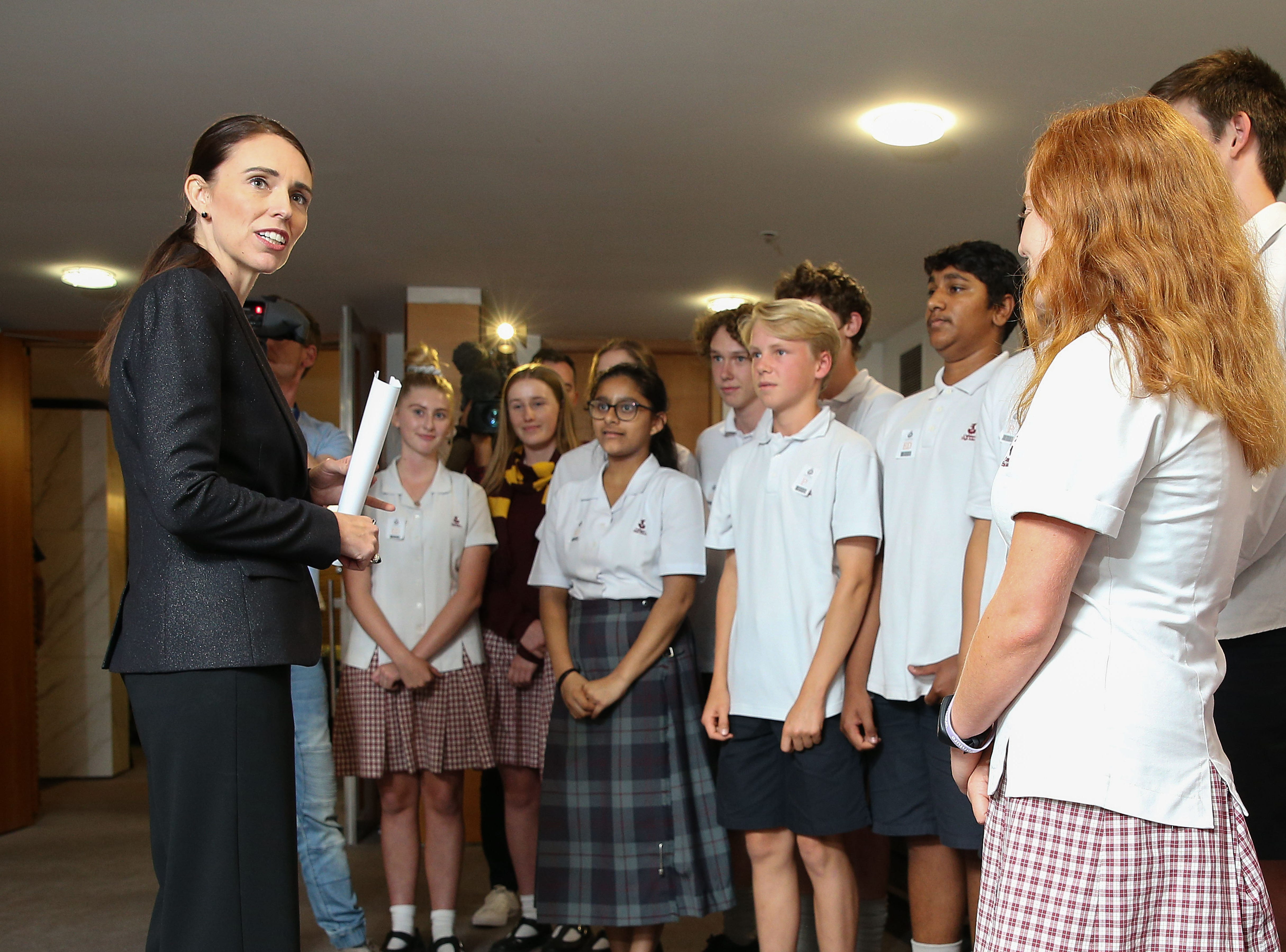 Prime Minister Jacinda Ardern stops to speak with school children before a press conference at Parliament on March 21, 2019 in Wellington, New Zealand.