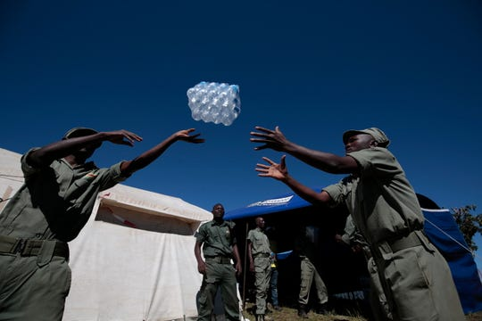 Relief in the form of bottled water is distributed to victims of Cyclone Idai in Chimanimani, Zimbabwe. The country's president, Emmerson Mnangagwa, declared Cyclone Idai a national disaster. Nearby countries such Zambia, Namibia, and South Africa have offered material help to the affected people and areas.