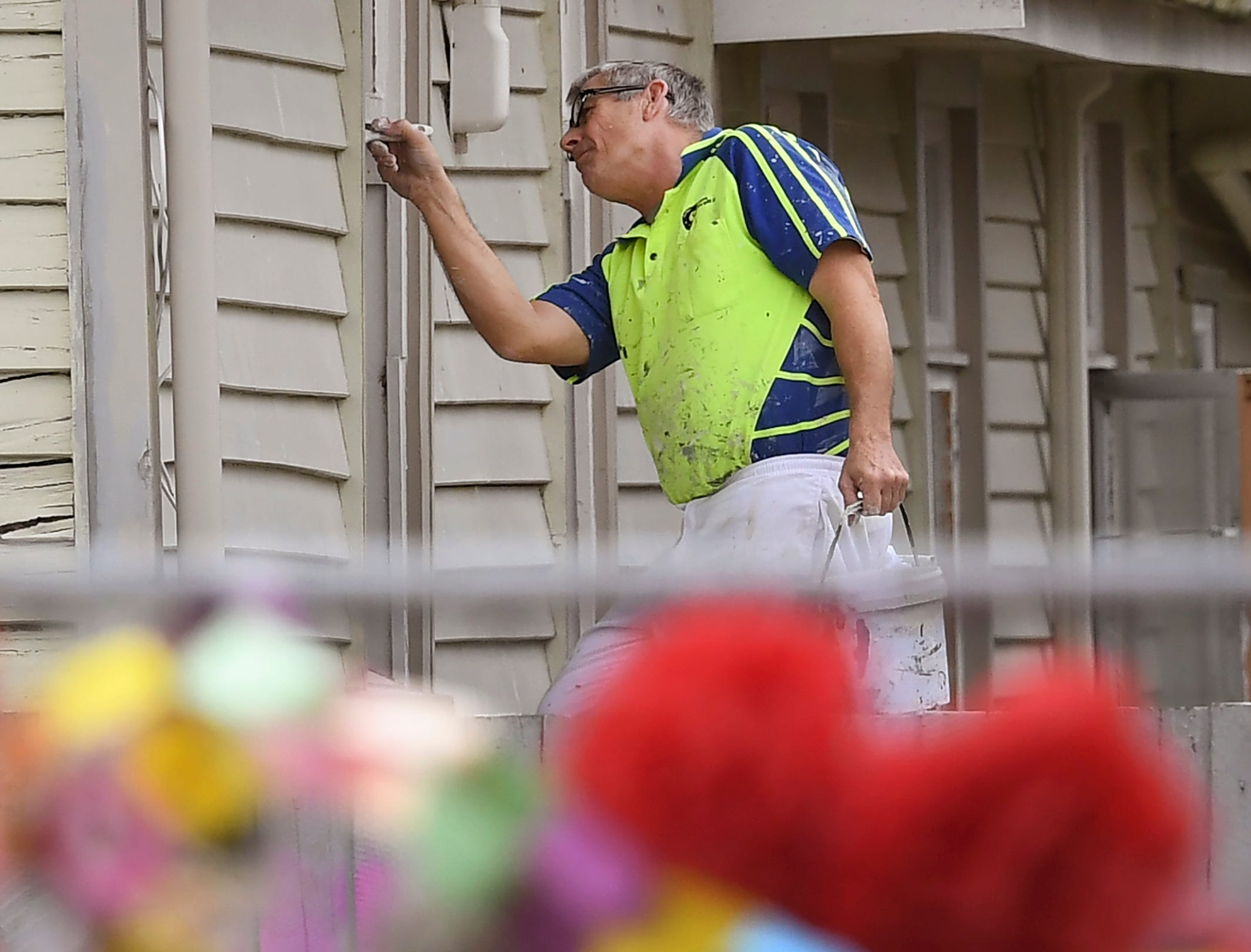 A painter works on the side of the Linwood Mosque in Christchurch on March 21, 2019, six days after the twin mosque shooting massacre that claimed the lives of fifty people.